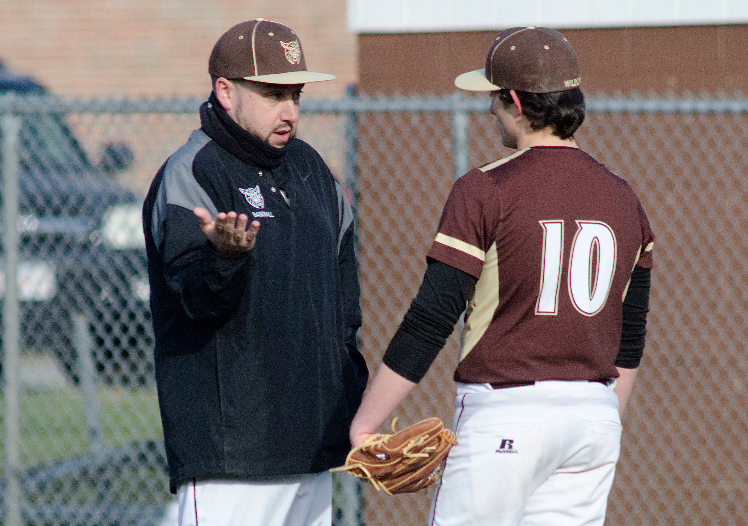 Head Coach Jason Pacheco talks to relief pitcher Ethan Carreiro during a time out.