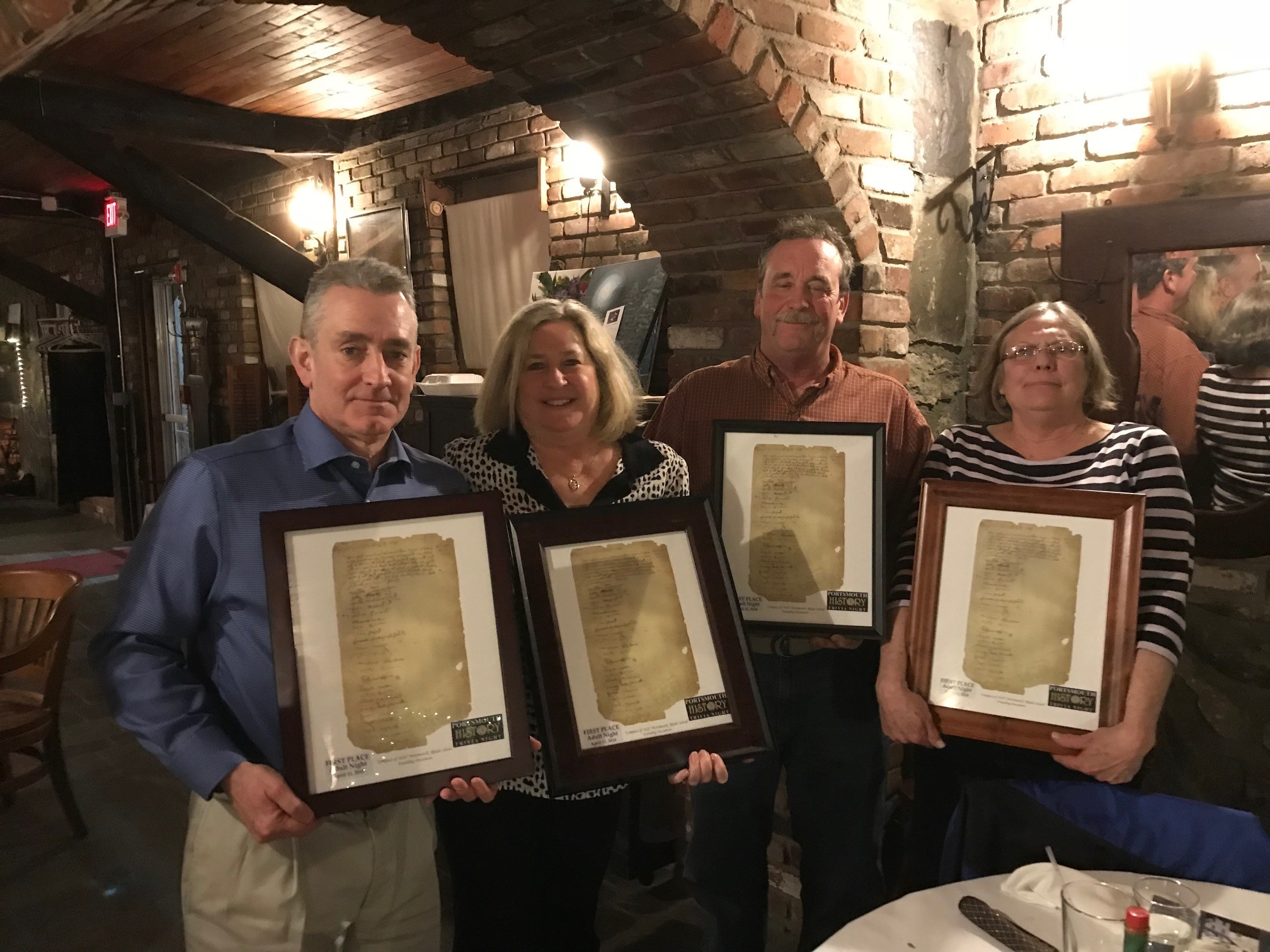 Members of the winning Stone/Thayer team pose with their framed copies of the Portsmouth Compact of 1638. From left are Mark and Terri-Lynn Thayer and Steve and Marcia Stone.