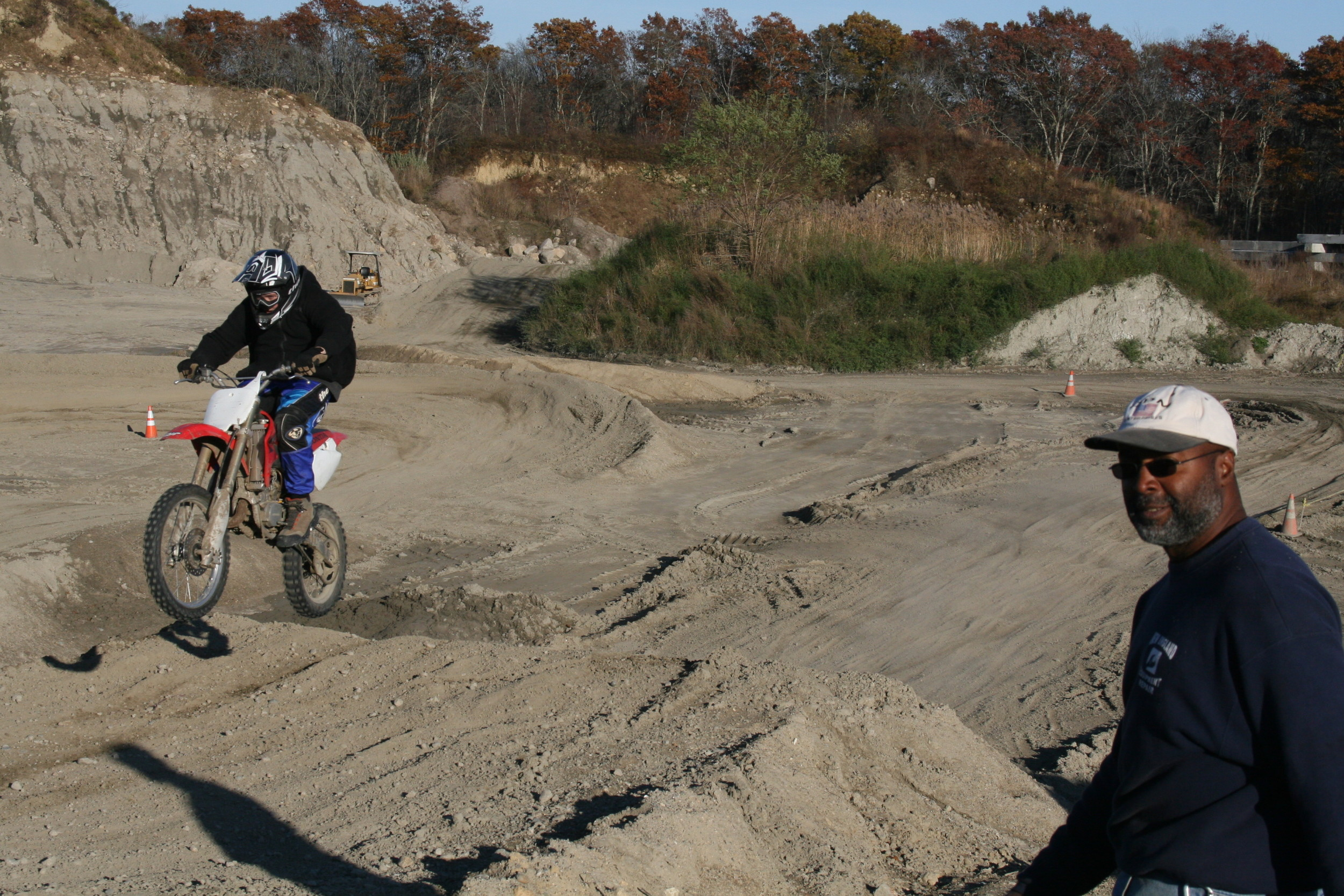 Ray Johnson (right) observes as a dirt biker a few years ago rounds the course at the site of the proposed motocross park the council failed to approve last week.