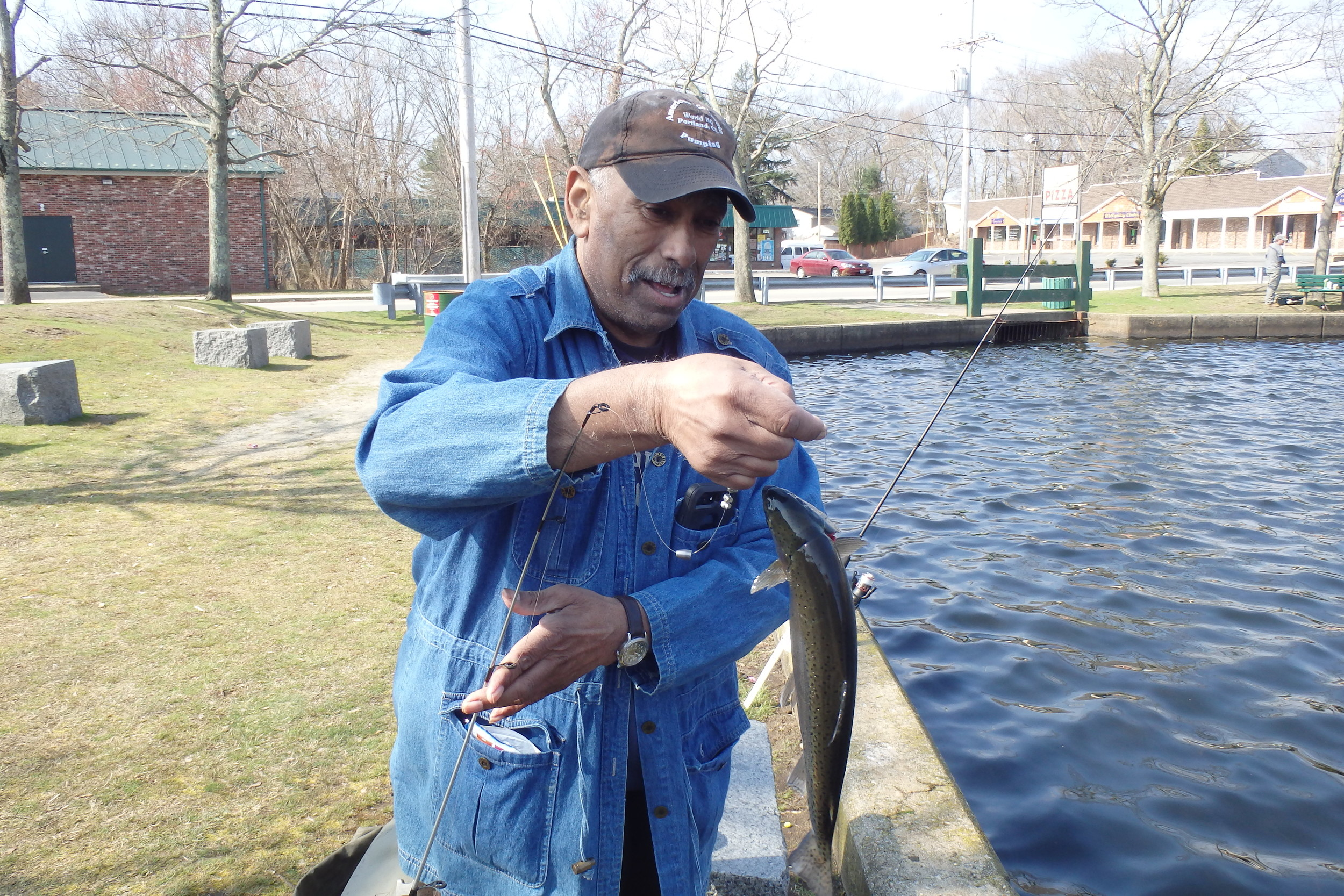 Steve Gomes of East Providence with a rainbow trout he hooked at Willet Avenue Pond.