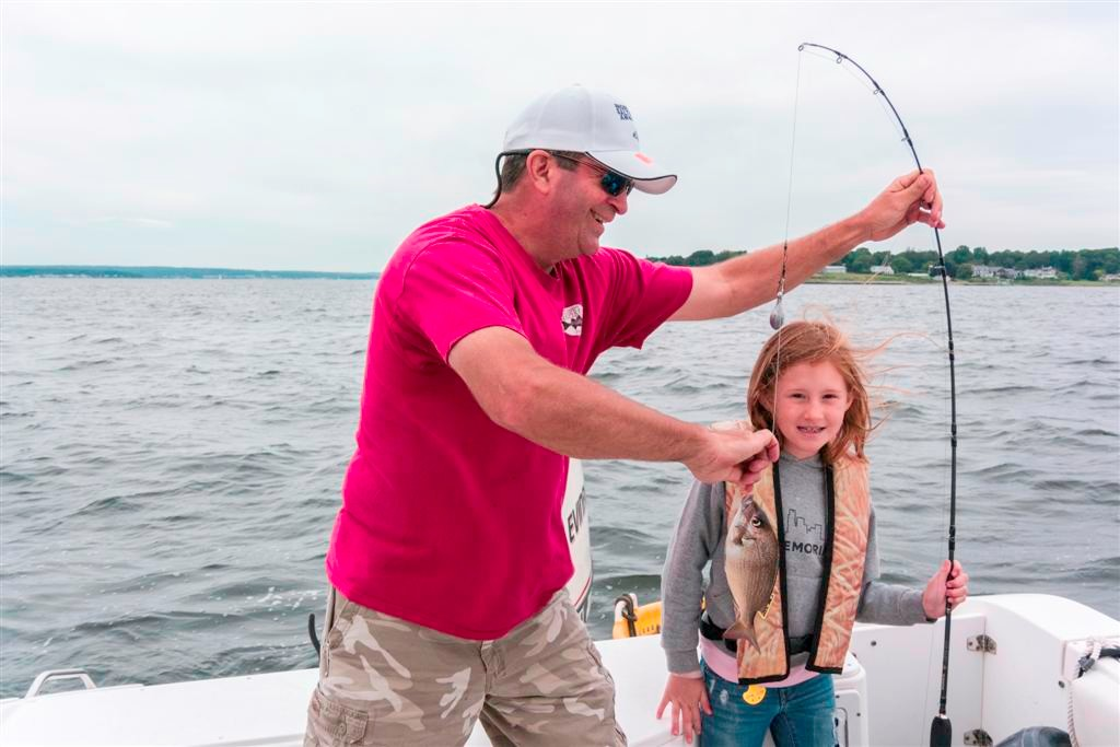 Michael Warner, RISAA volunteer, helps a fishing camp participant land their catch.