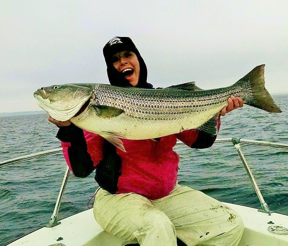 "Kerry Sampson of Warwick with the 35"" striped bass she caught earlier this week in the East Passage of Narragansett Bay."