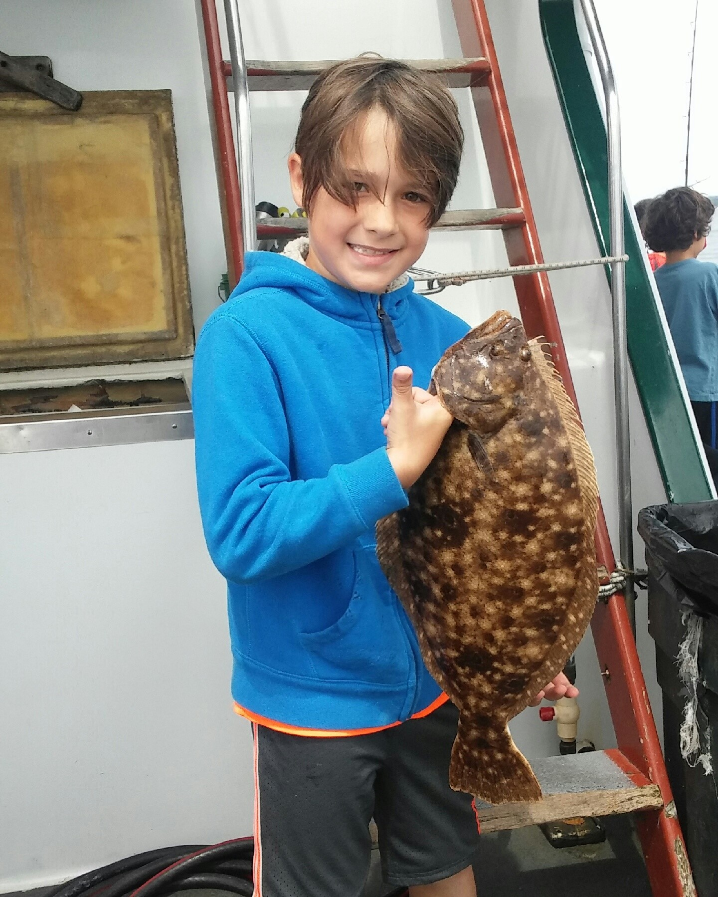 "Noah Blasi of Warwick with the 22"" summer flounder (fluke) he caught at the RI Saltwater Anglers Association fishing camp this week on the Seven B's party boat."