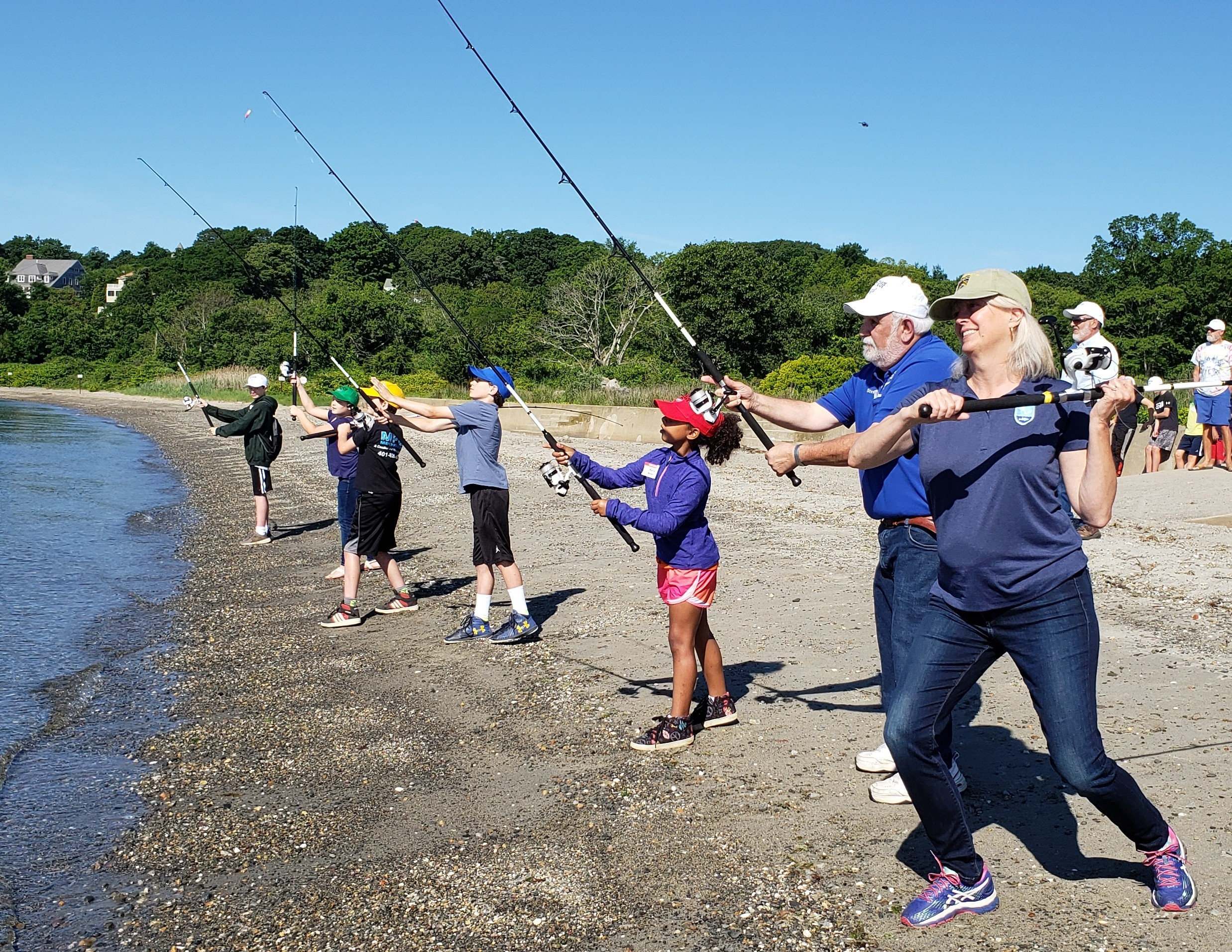 Janet Coit, DEM Director; Steve Medeiros, RISAA president/camp director; and camp participants held a cast-off to open the third annual RISAA Youth Fishing Camp.
