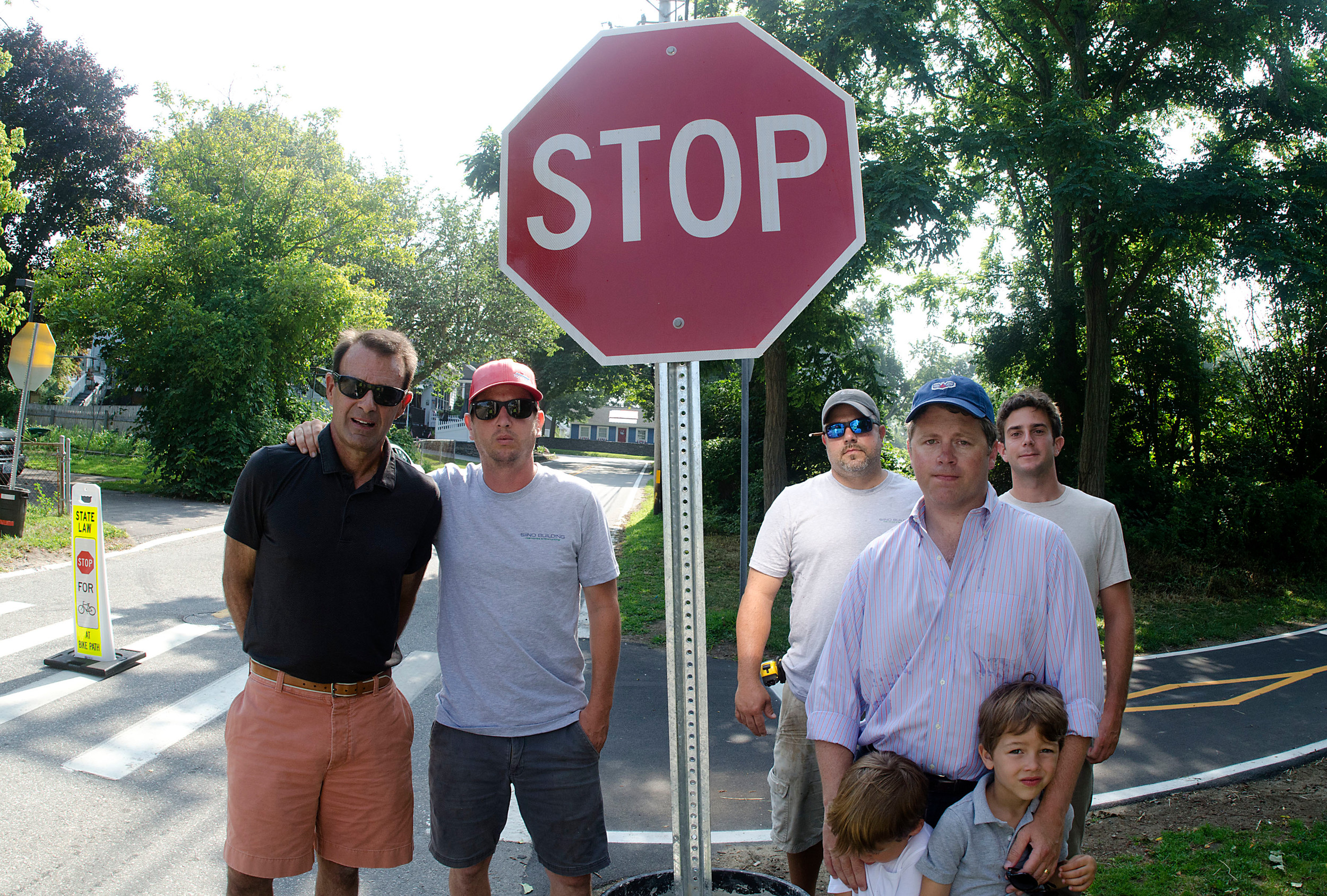 From left, Matt Hayes, Mike Siino, Pedro Ramos, Angus Davis  and Nick Campagna pose in front of one of the stop signs that they put up on Poppasquash Rd. on Friday morning.