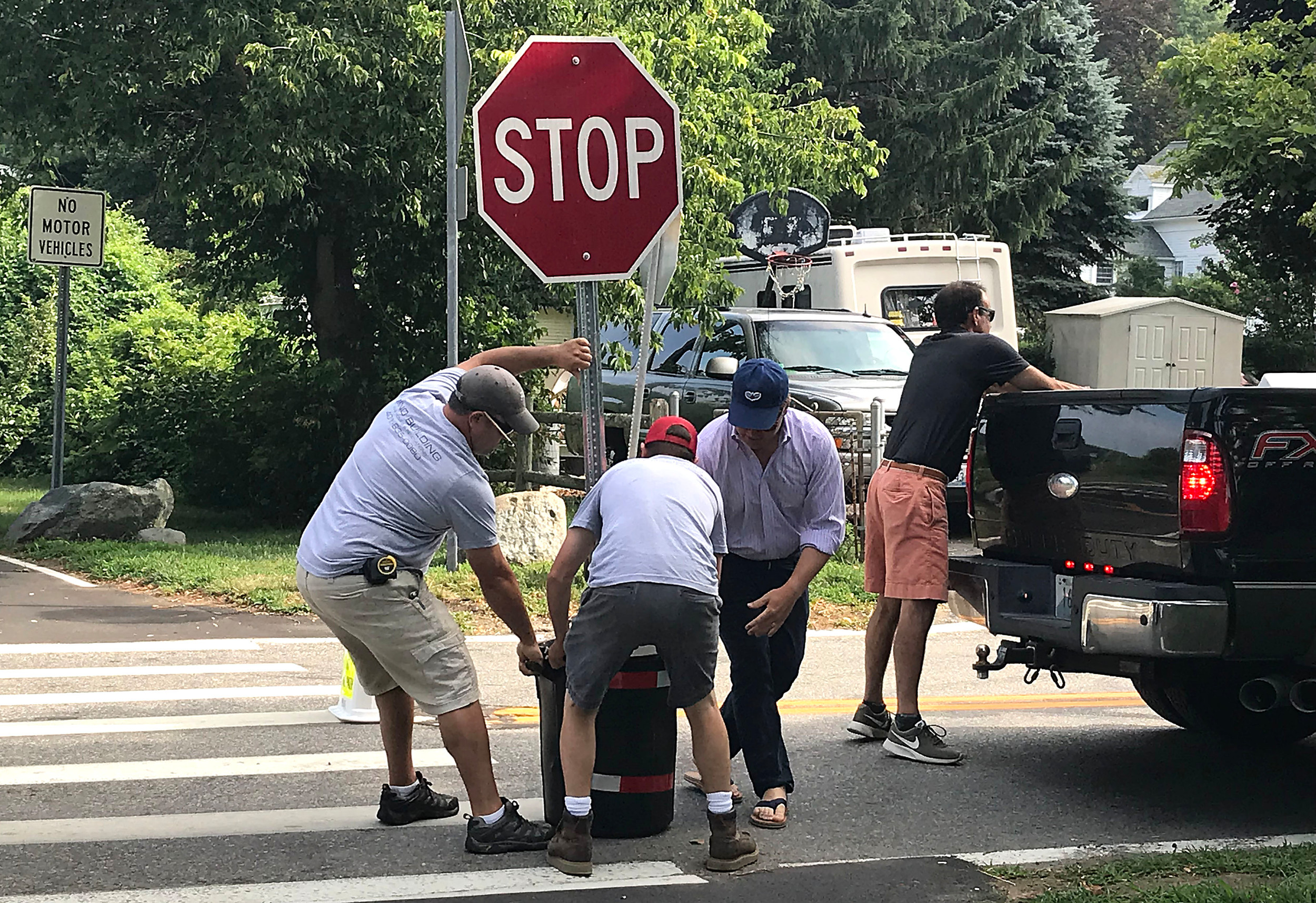 Bristol residents drag a temporary stop sign onto Poppasquash Rd. on Friday morning.