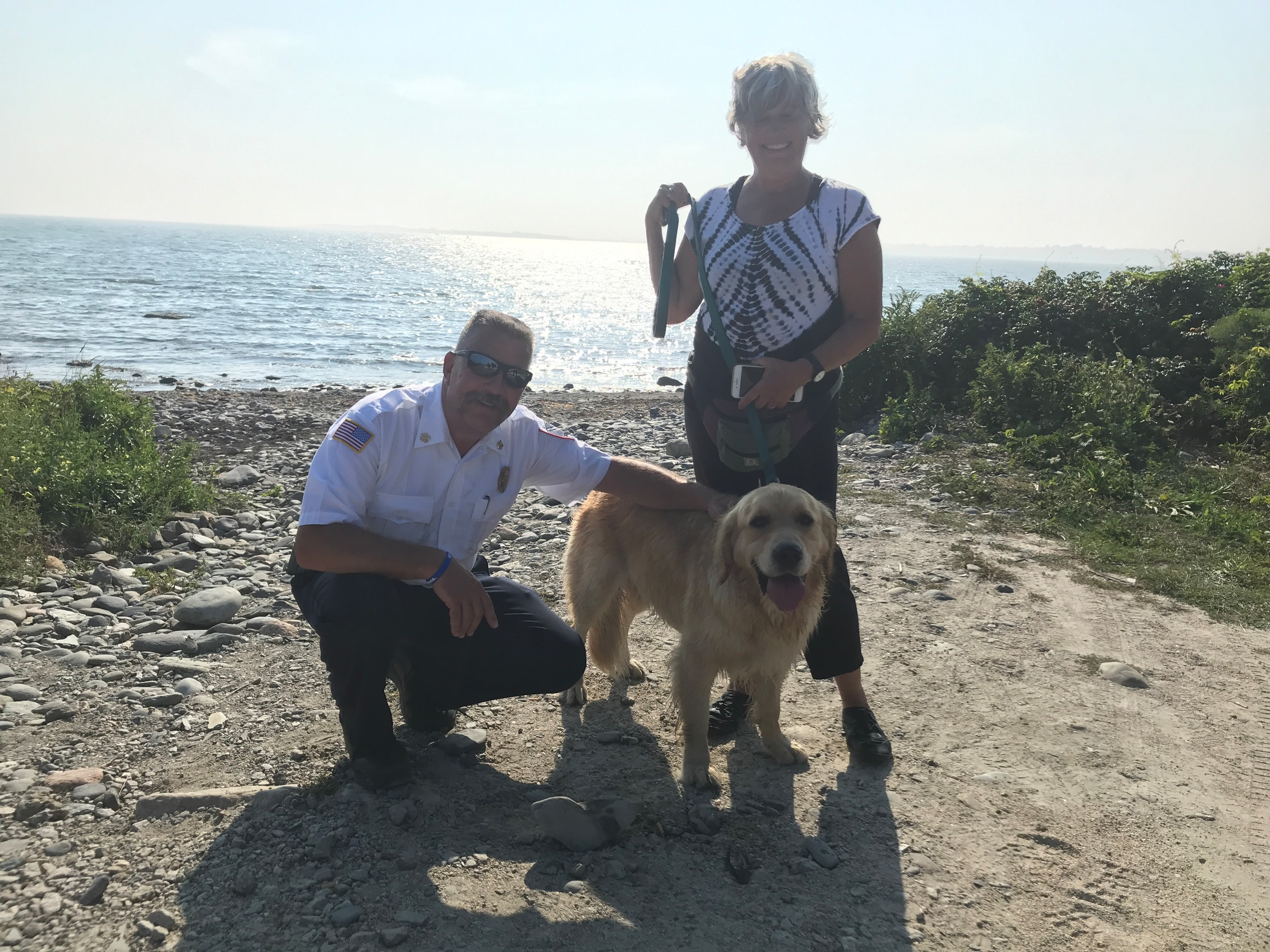 "From left, Richard Petrin, Little Compton Fire Department chief, Fenway Fossel, and Jana Porter, Fen's ""mother,"" celebrate Fen's rescue from the Sakonnet River where he disappeared Tuesday in small craft advisory waters while chasing a seagull."