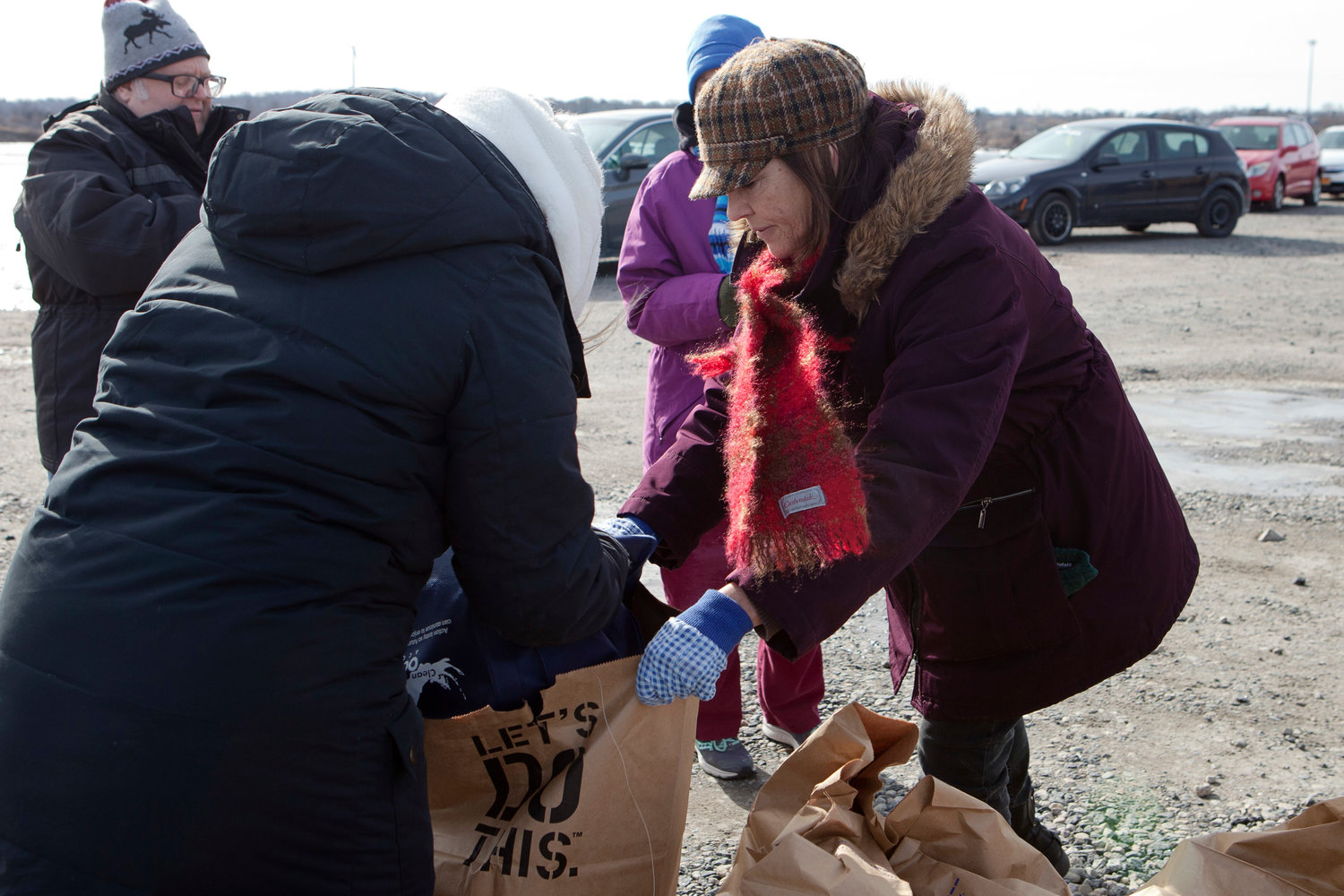 Diane Andrews (right) helps fill a bag with trash collected at Gull Cove.