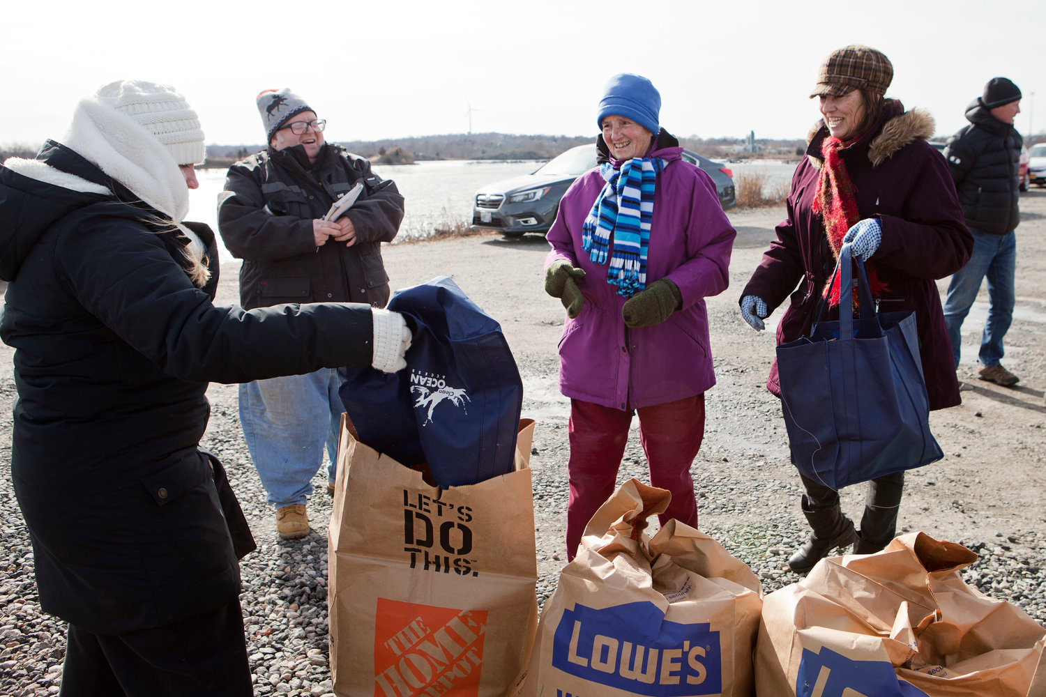 Jessie Frascotti (left), program coordinator of Clean Ocean Access, dumps trash collected by volunteers into leaf bags. At right are Mary Silveria and Diane Andrews.
