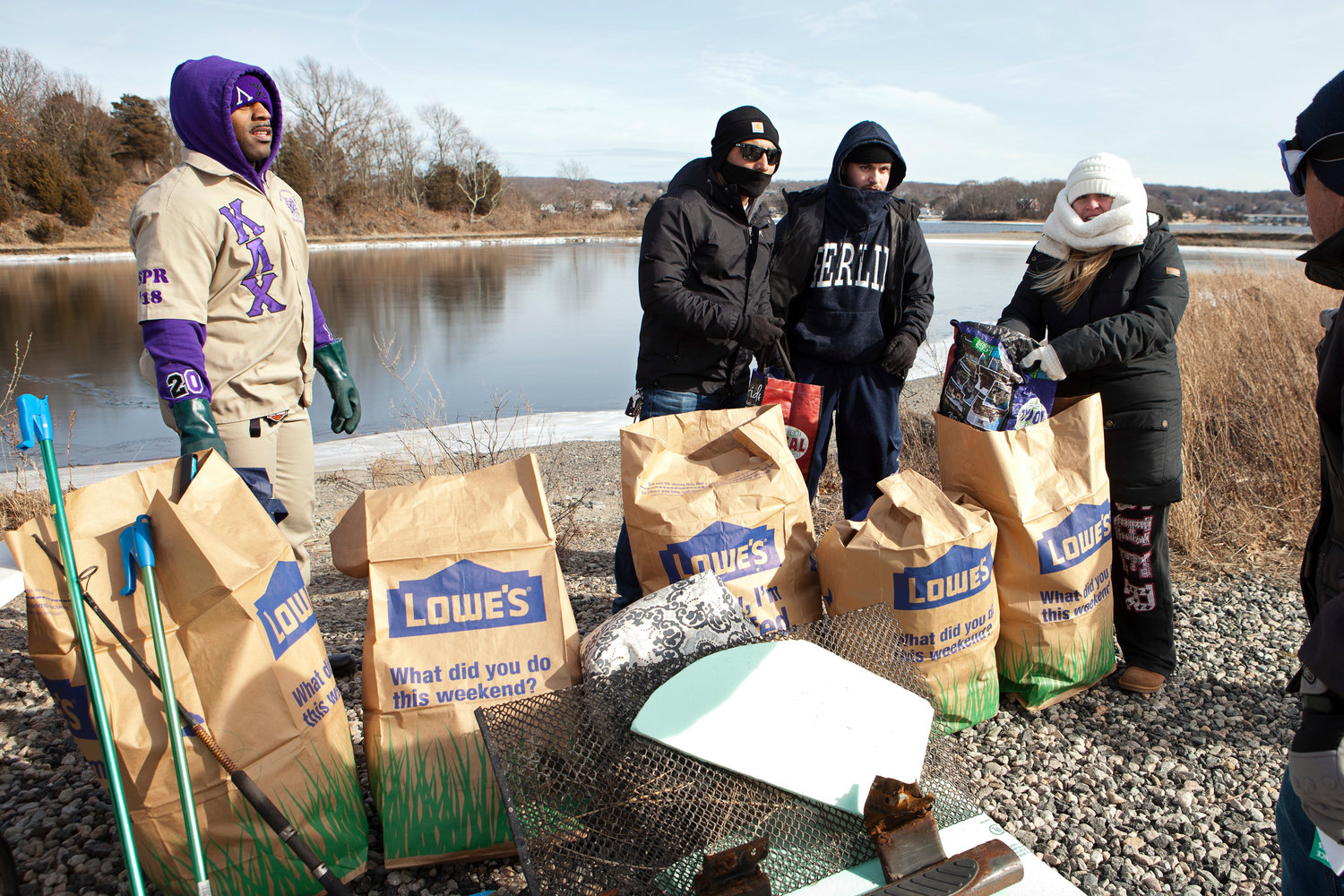 Darius Grays, Jinal Patel and William Zanolli (from left) help program coordinator Jessie Frascotti fill bags with trash.