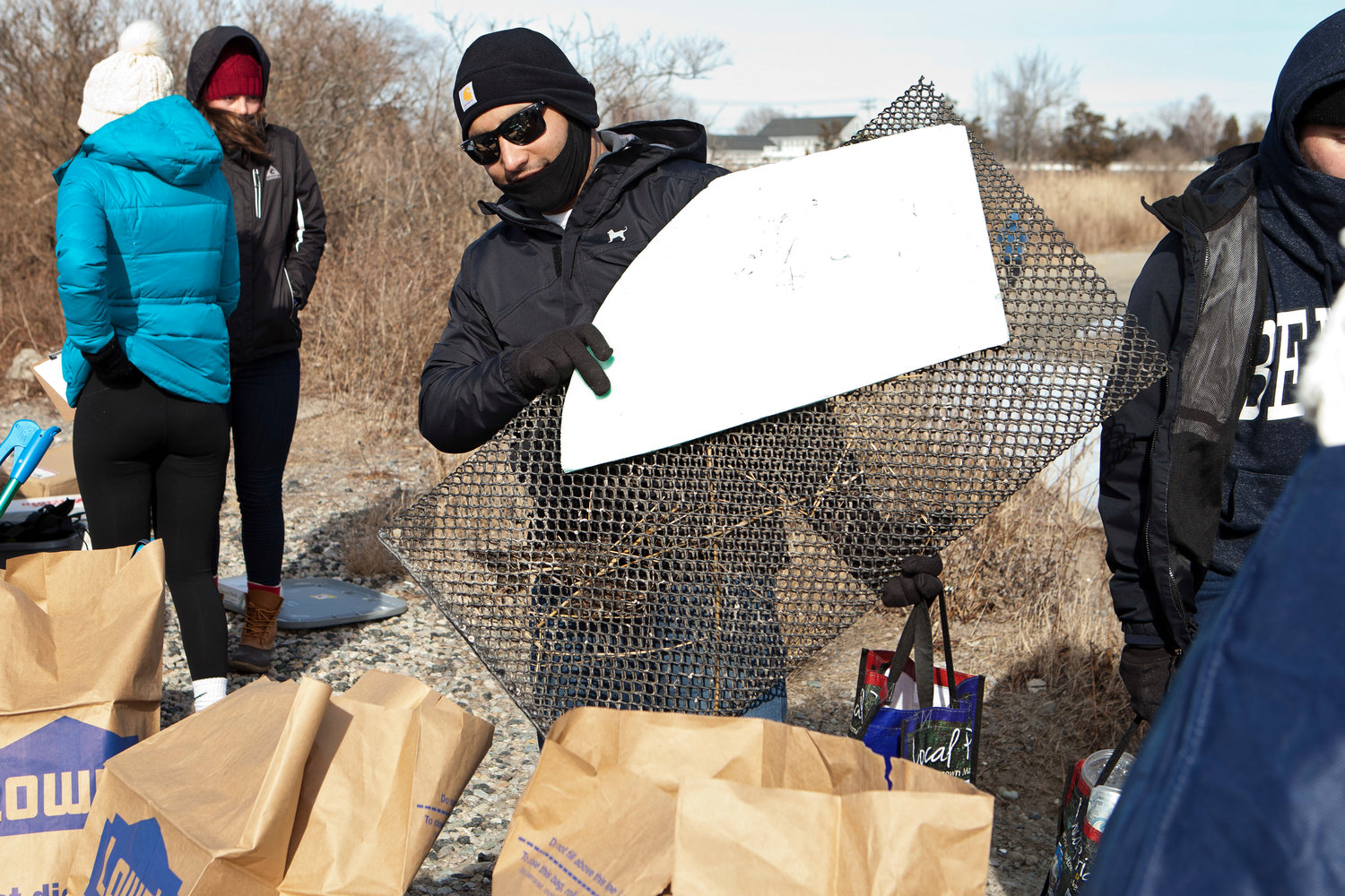 Jinal Patel carries trash he collected, including a large piece of foam and a metal grate, to the collection point.