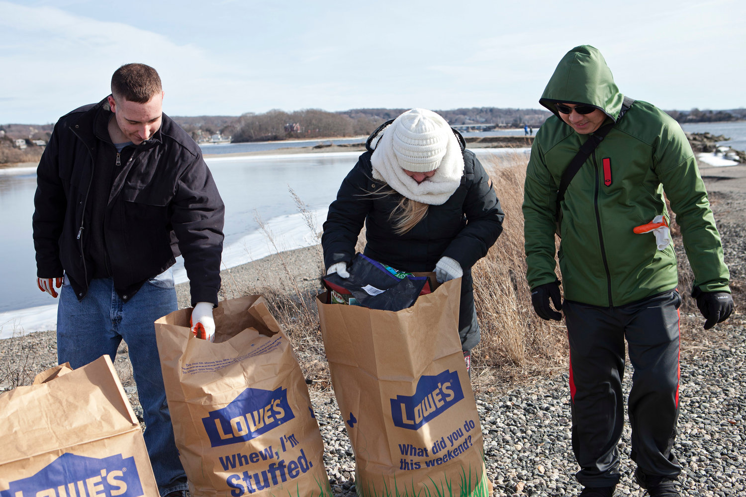 Nick Korpics (left) and Thomas Molina (right) help program coordinator Jessie Frascotti fill bags with trash.