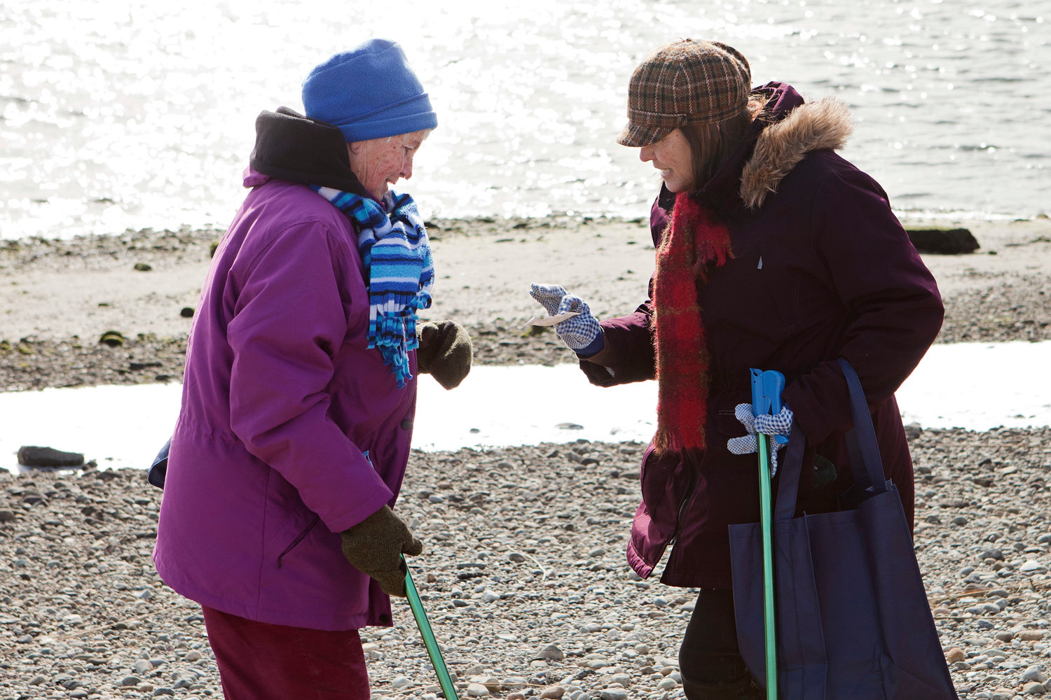 Mary Silveria (left) and Diane Andrews examine a piece of trash found at Gull Cove.