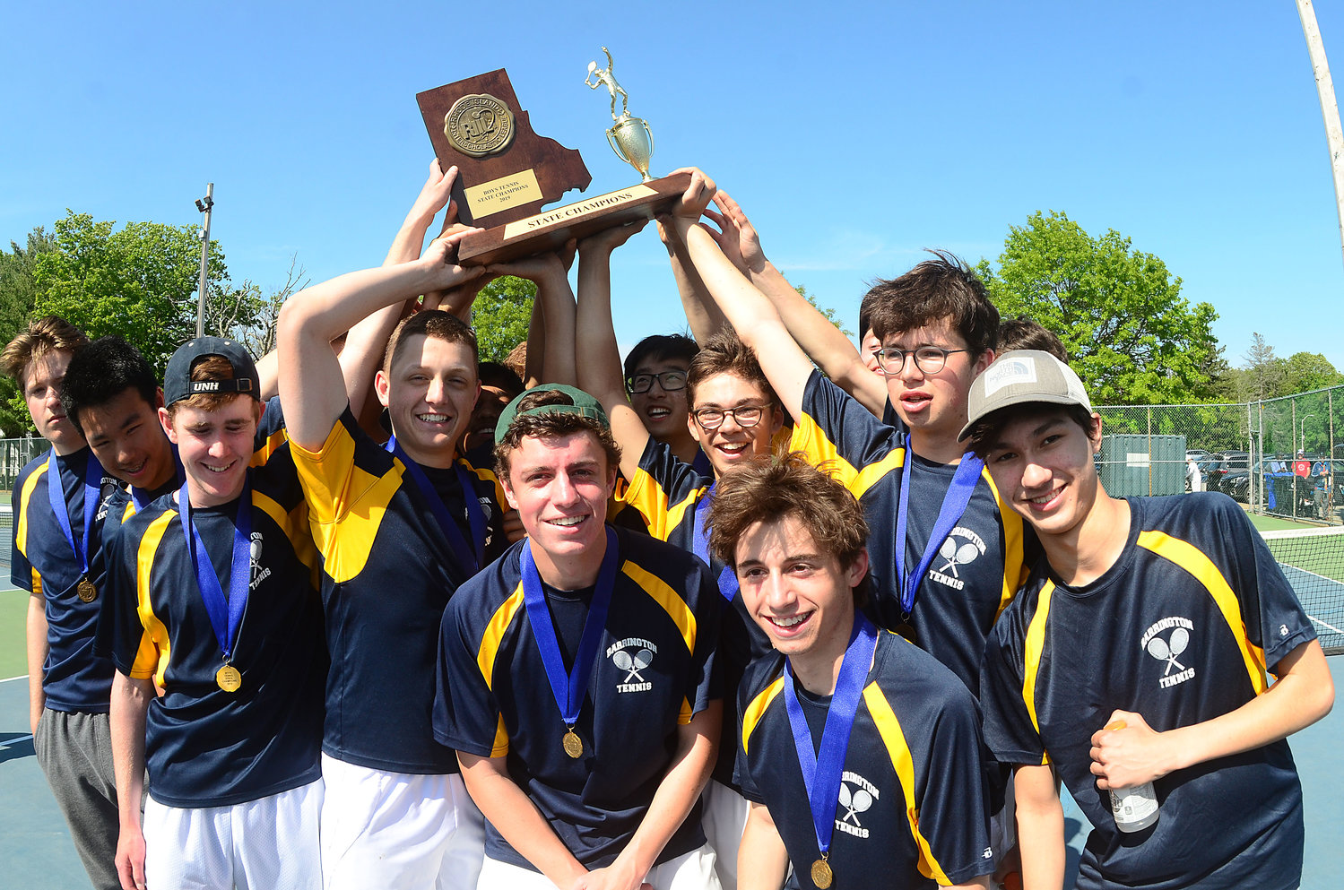 Members of the Barrington High School boys tennis team celebrate an undefeated season and state championship following their finals win over Wheeler on Saturday.