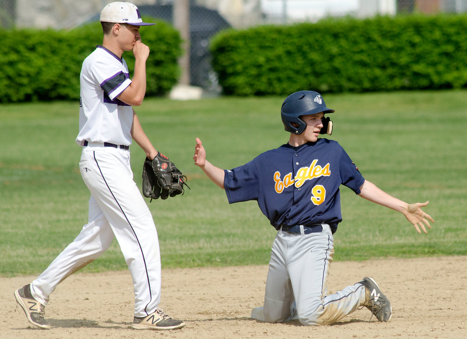 Huskies shortstop Cam Santerre blows into his hand after tagging out Eagles baserunner Sam Turner.