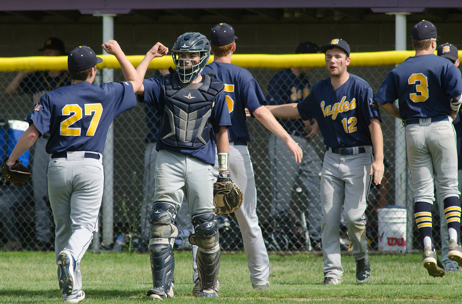 Elijah Kraemer (left) Jack Kriz, Henry Johnson and others celebrate with teammates after getting out of a rough inning.
