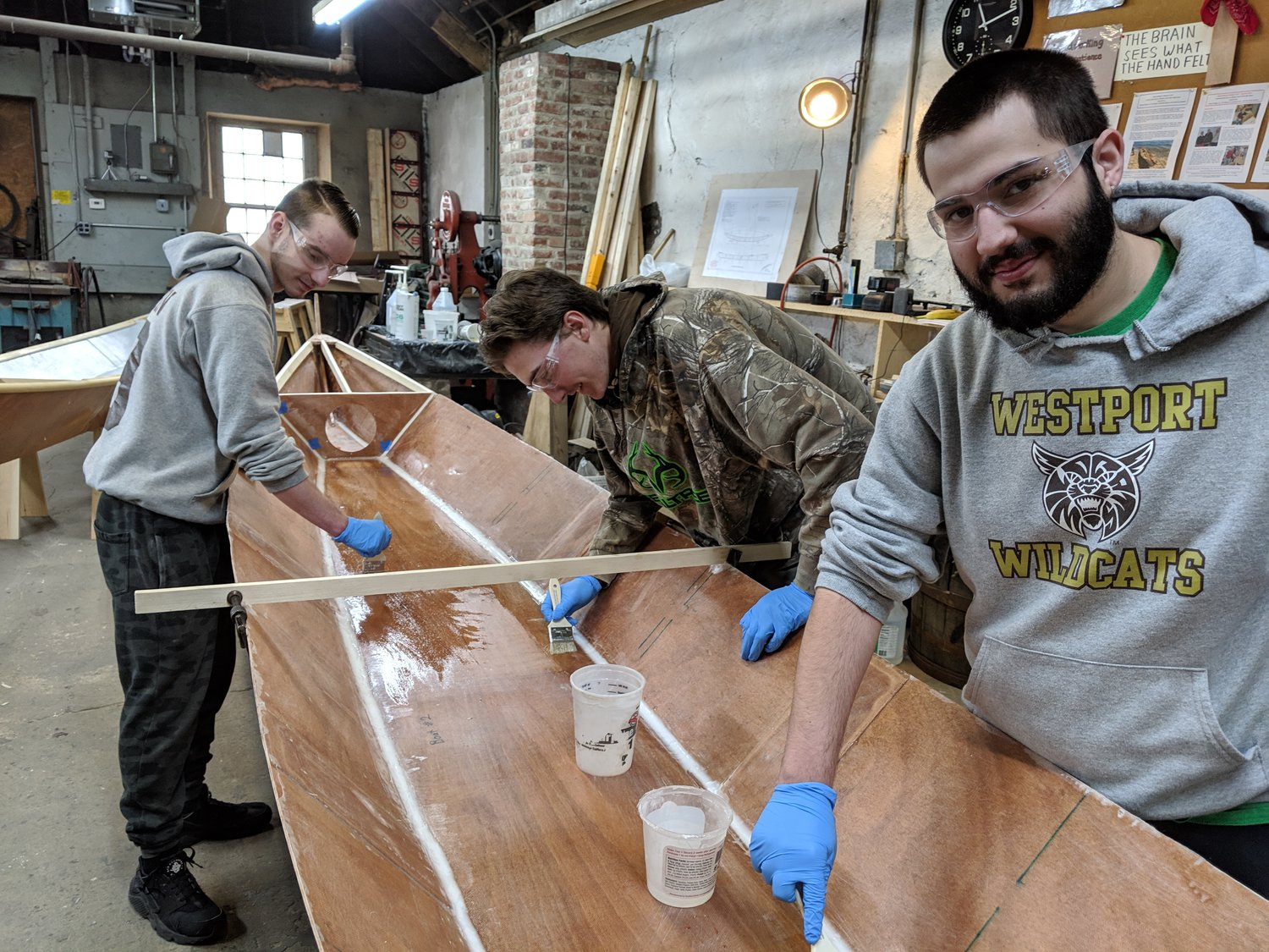 Dylan Amorin, Cody Smeaton, and Zachary Lavoie apply a skim coat of epoxy.