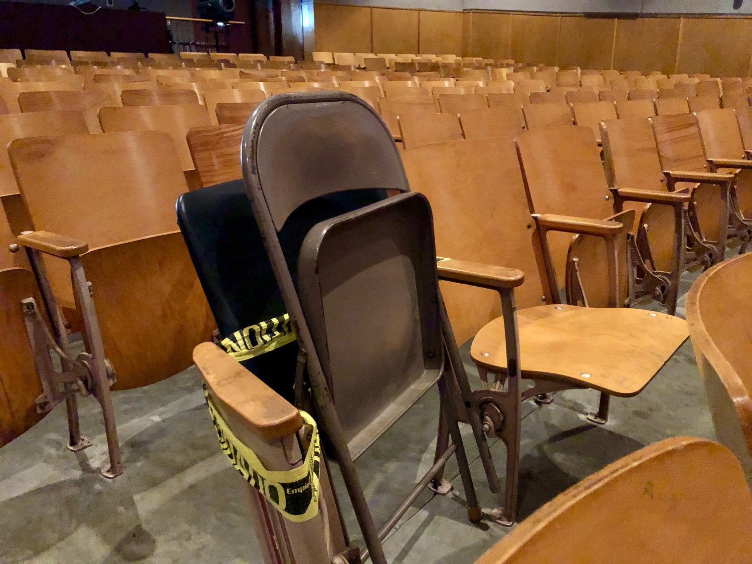 A metal folding chair blocks one of the original wooden chairs in the Portsmouth High School auditorium, indicating it's not safe to sit in. All of the chairs will be replaced starting next week.