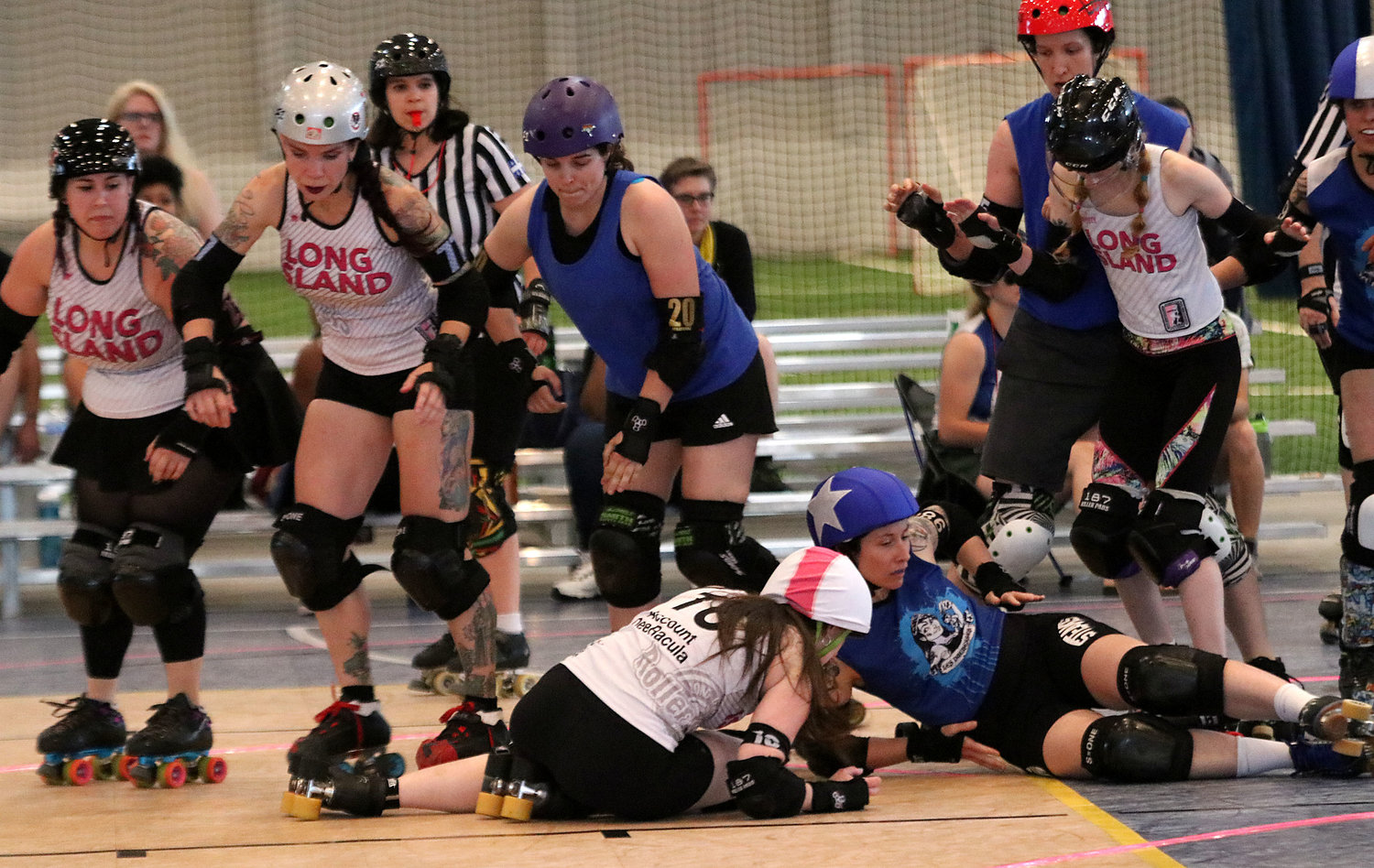 Team members look on as Account DeeRacula of the Roller Rebels (middle) and Lo Dalton of Les Duchesses (right) hit the floor after a collision during their bout in the annual Rhodey Robin Roller Derby Tournament at Long Plex on Saturday.
