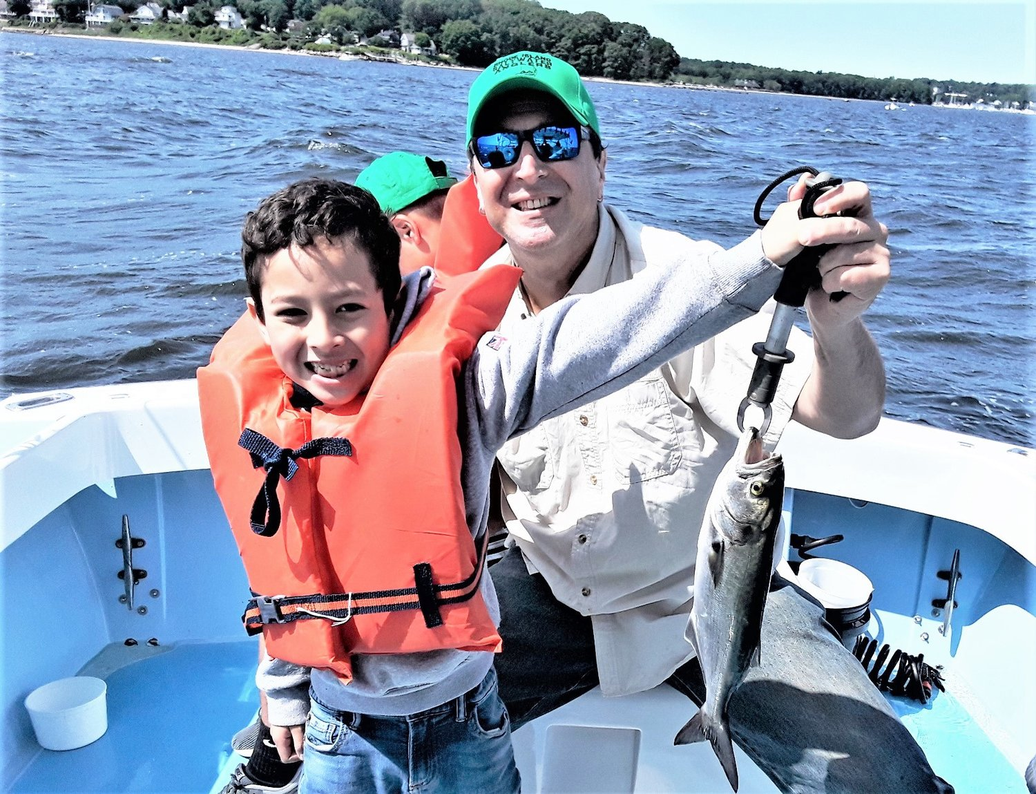 Take-A-Kid Fishing Day a Success: Alexander, a Cub Scout from Providence, with a bluefish he caught Saturday with the help of Steve Brustein, a RI Saltwater Anglers Association volunteer from West Warwick.