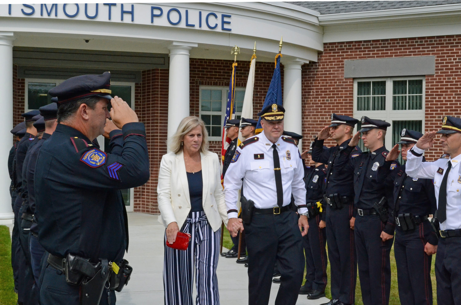 Retiring Police Chief Thomas Lee is saluted by officers as he walks out of the police station with his wife, Mary, a police officer with the Boston Police Department.