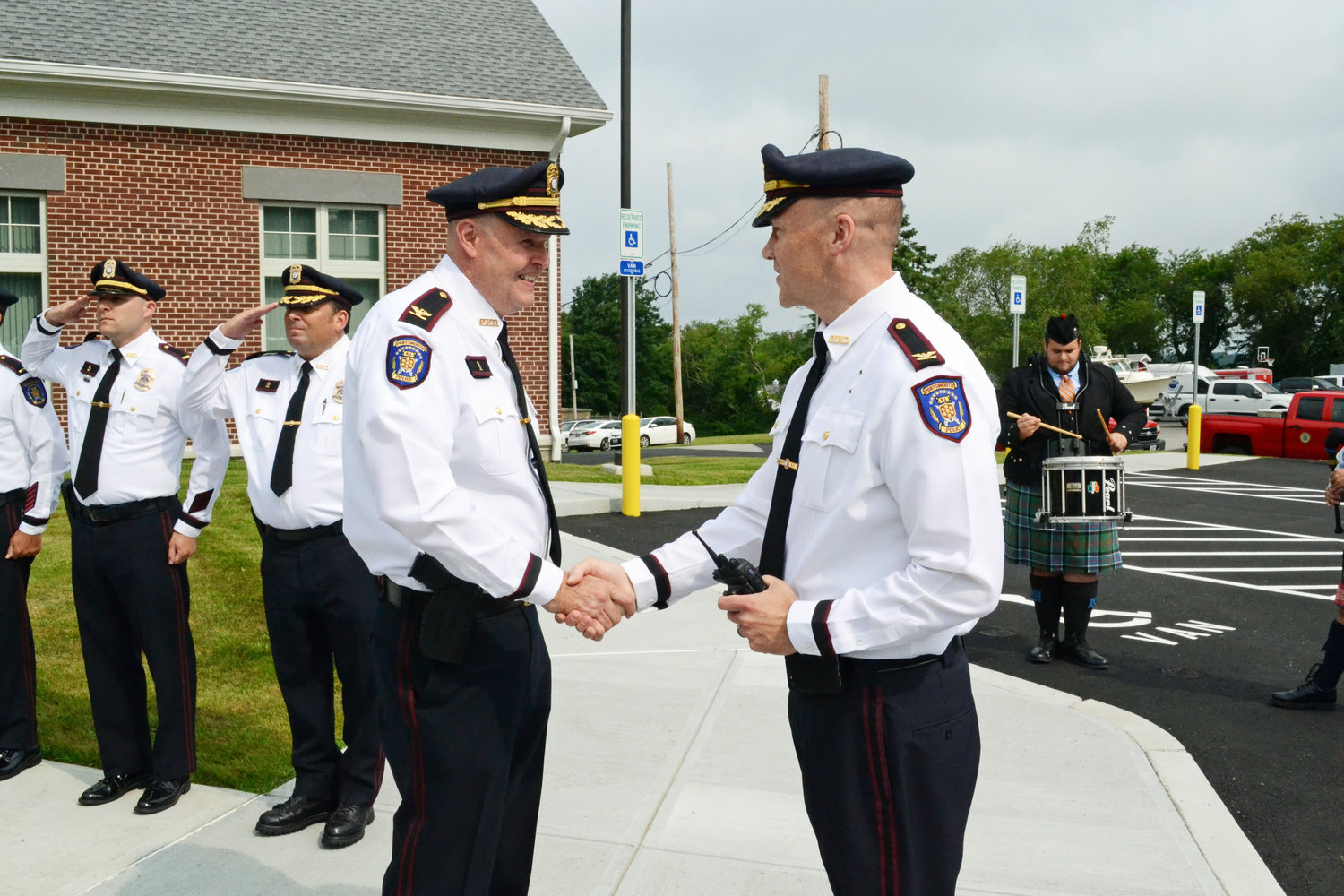 "Chief to chief: Retiring Police Chief Thomas Lee (left) greets his successor, Chief Brian Peters, during the former's ""walk-out"" ceremony at the police station Thursday morning, July 11."