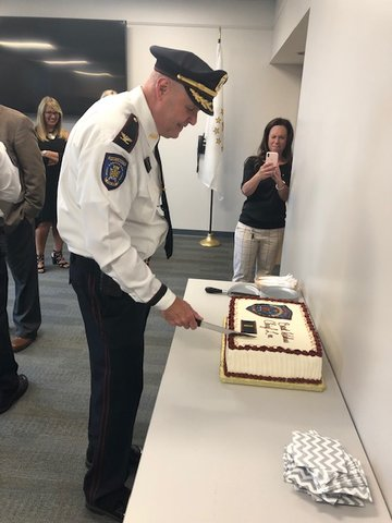 Chief Lee cuts a cake in his honor, as records clerk Tracy LePage snaps a photo.