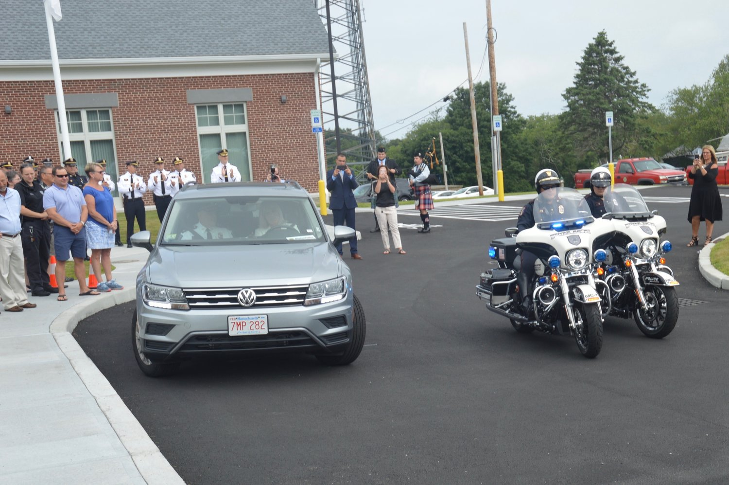 "Detective Jacob Silva and Officer Maddie Pirri, members of the Portsmouth Police Department's new Motorcycle Unit, escort retiring Police Chief Thomas Lee (in passenger seat of car at left), from the police station at the end of his ""walk-out"" ceremony."
