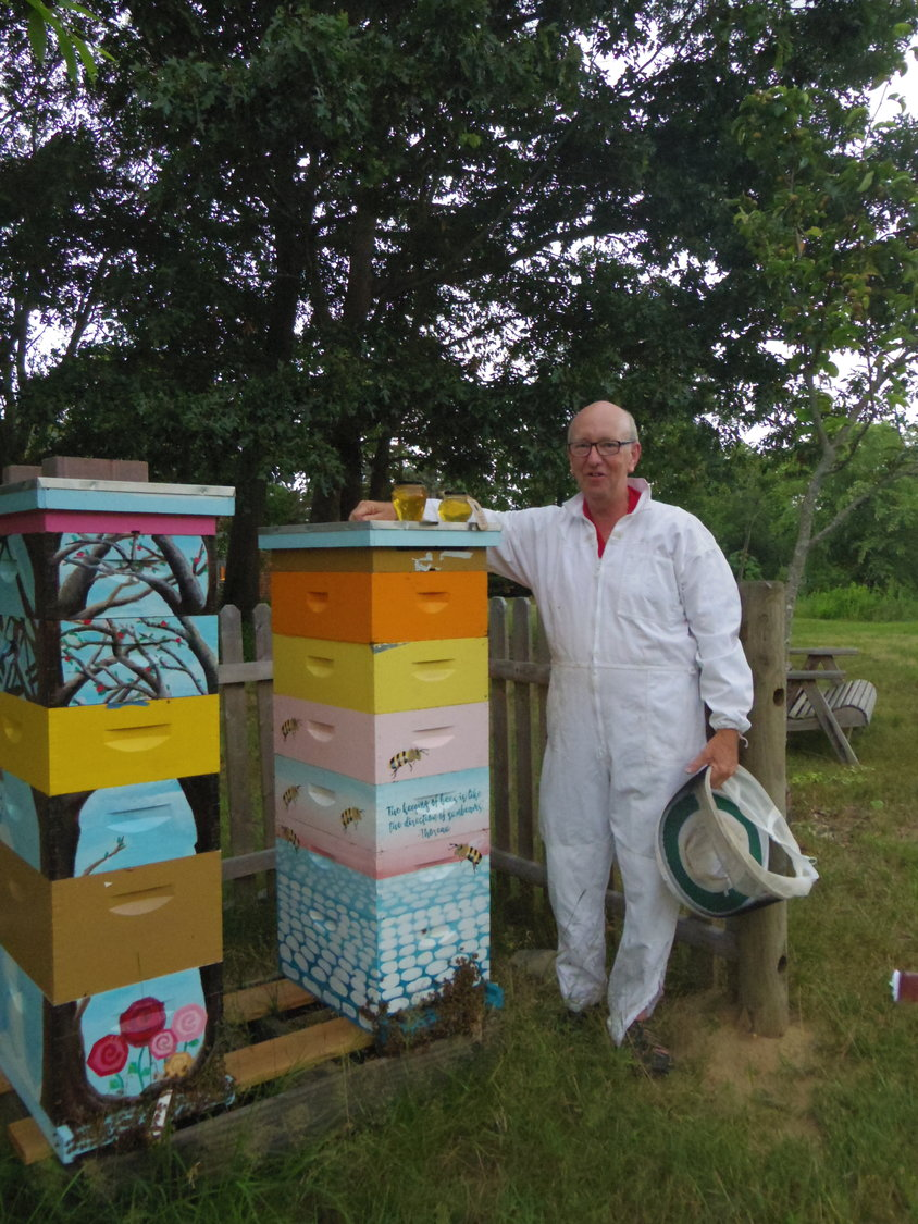 Master beekeeper Dane Pursley stands with the hive boxes at the Barrington Farm School.