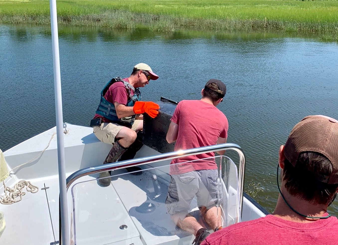 Warren Harbormaster Ed Cabral (center) helps spread oysters Friday in Chase Cove.