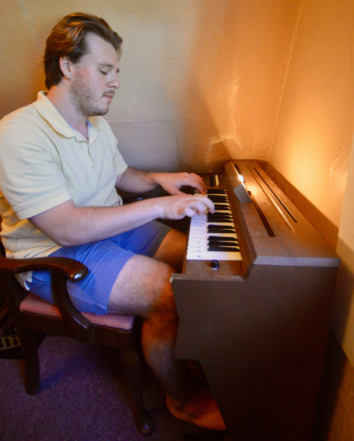 Nicholas Quigley, who teaches music to grades 5-8 at Atlantis Charter School in Fall River, plays a vintage chord organ at his Bristol Ferry Road apartment last week. The instrument, a smaller version of a regular organ, was popular in the '60s and '70s.