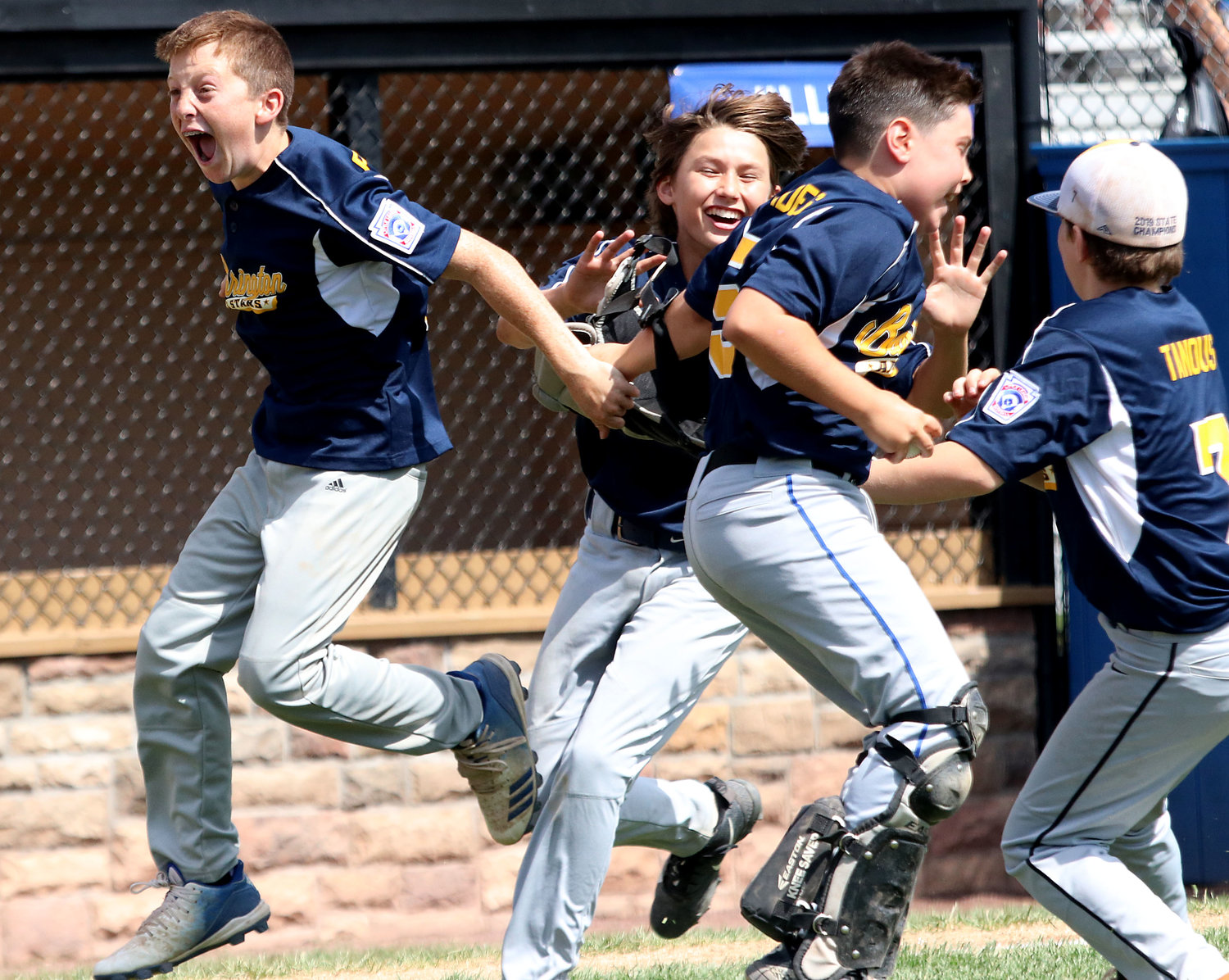 Owen Pfeffer, James Calderella, Bumpy Promades and Lucas Tanous celebrate after Barrington beat New Hampshire 6-4 to win the New England Regional Championship in Bristol, Conn., on Saturday afternoon.