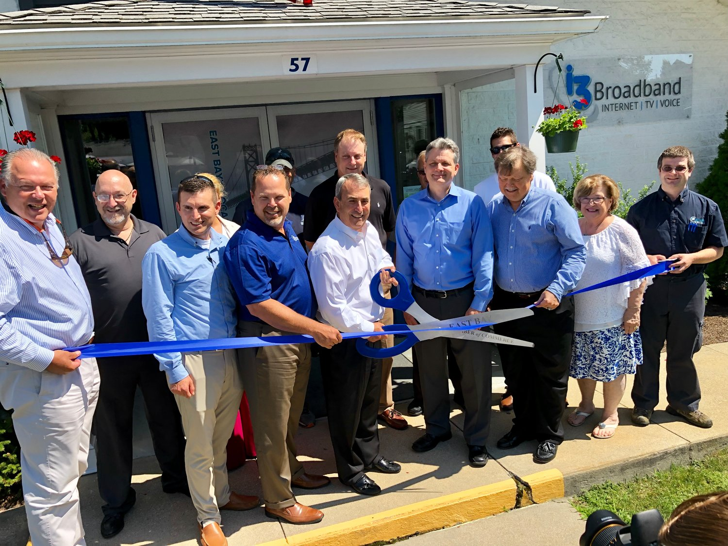 Sam Valencia (holding scissors) cuts the ribbon on the re-naming of Full Channel to i3 Broadband, Thursday afternoon in Warren.