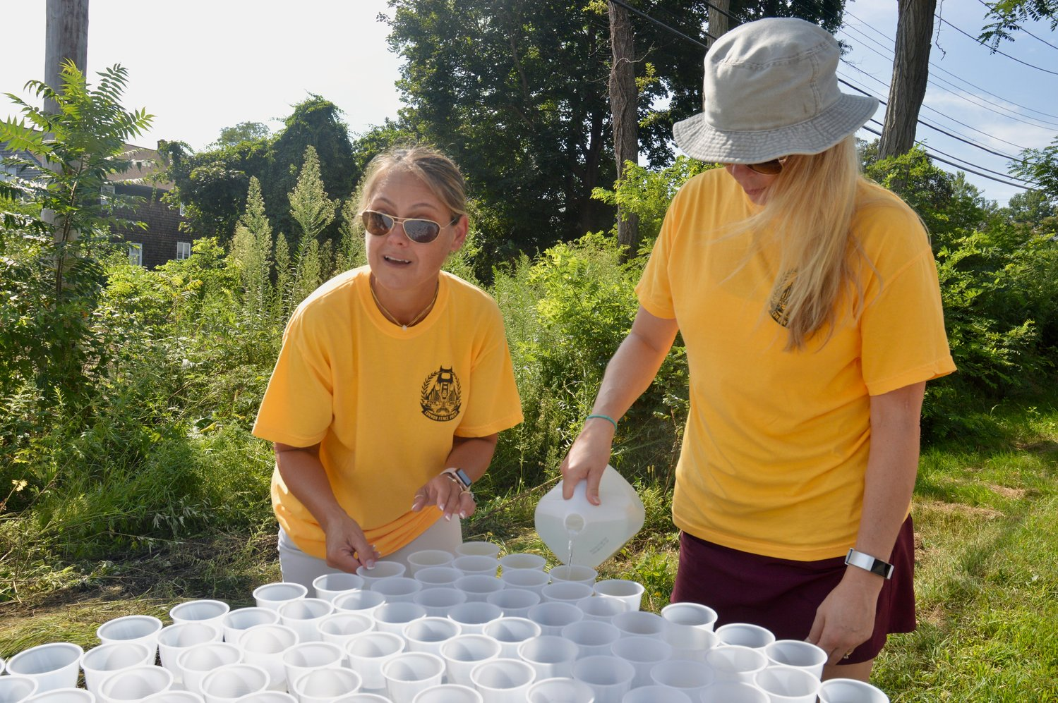 Volunteers Christy Brennan (left) and Tammy Harrigan fill water cups which were handed out to runners during the race.