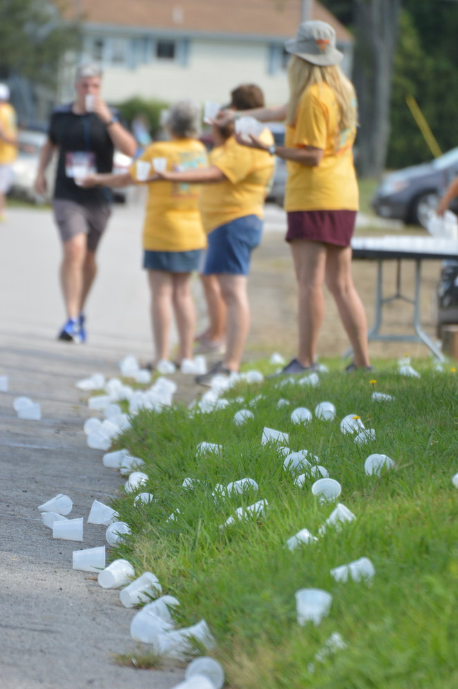 Empty water cups are scattered on the ground after runners pass a volunteer refreshment station.