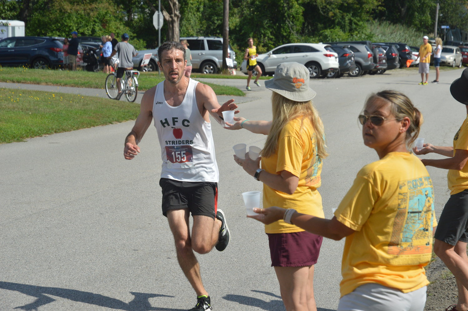 TJ Unger of Westwood, Mass., grabs a cup of water in the early stages of the race. He would finish in third place in a time of 27:59.