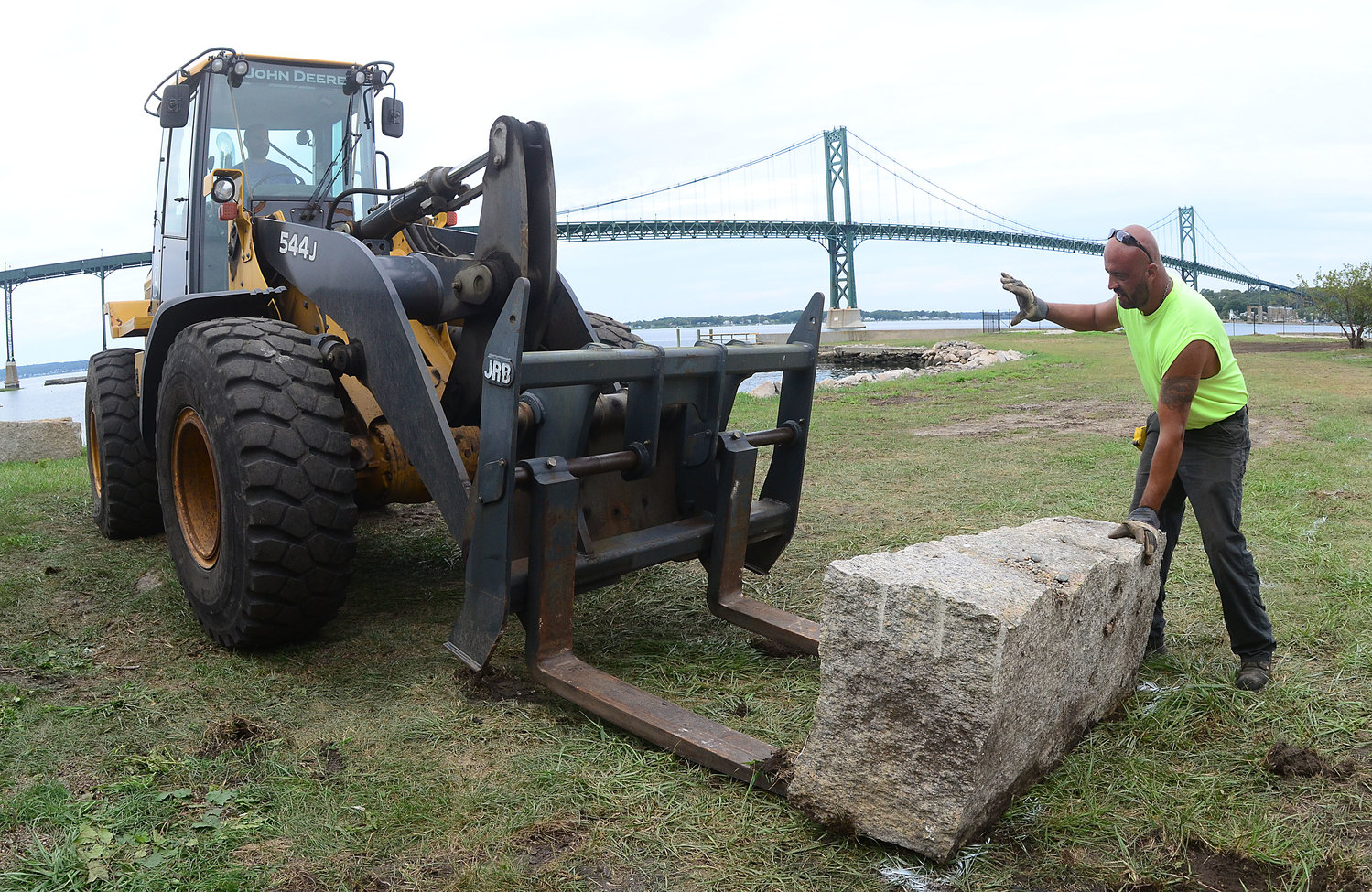 Backhoe operator Ryan January lifts a granite stone as Mike Corvin (right) guides it into place.