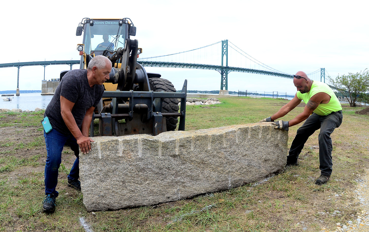 Backhoe operator Ryan January lifts a granite stone at Mt. Hope Park as Paul Rodrigues (left) and Mike Corvin guide it into place. The three men work for the Department of Public Works, which is getting the new waterfront park prepared for its opening to the public.