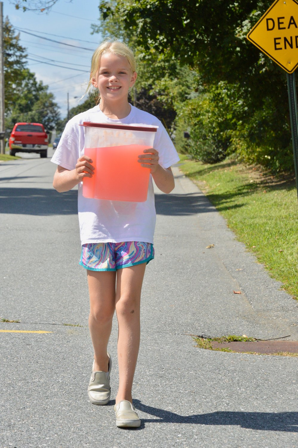 Gwen Schaub carries a container full of pink lemonade from her Windward Drive home to the lemonade stand at the corner of Linda Avenue.