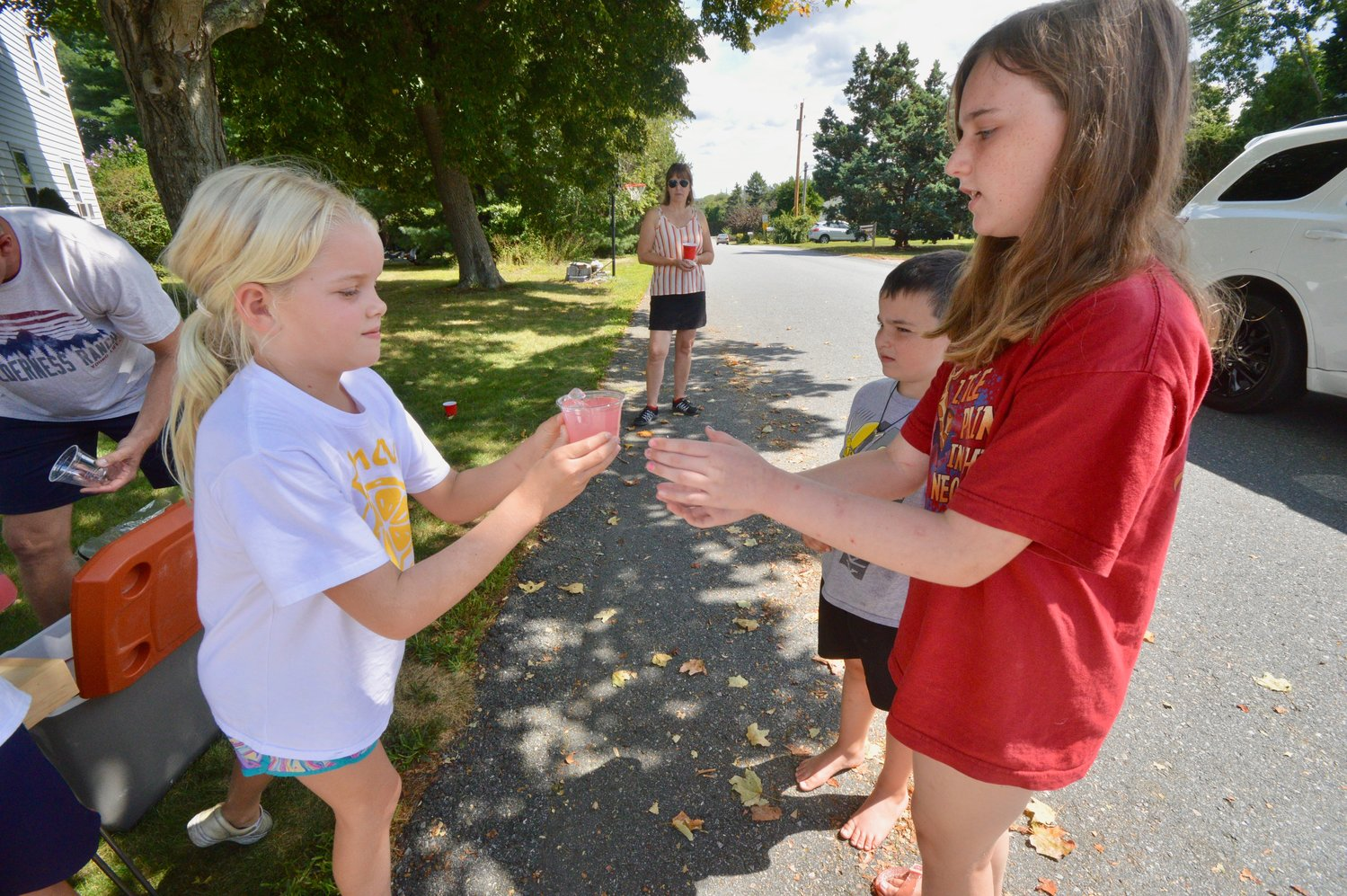 Gwen Schaub (left) hands a cup of lemonade to Olivia Purdy as Andrew Purdy waits for his glass. The Schaub family held the fund-raiser for Africa New Life's Meals for School Kids in Rwanda program.