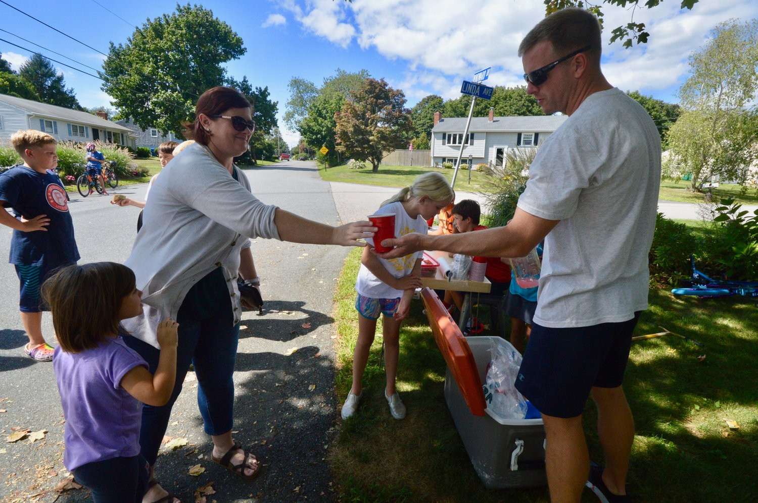 Jennifer Ferreira takes a cup of lemonade from Aaron Schaub for her 4-year-old daughter,  Avery (left). Ms Ferreira is a classmate of Mr. Schaub's at the Naval War College.