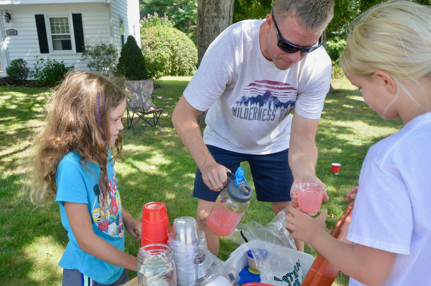 Aaron Schaub hands his daughter, Gwen, a cup of lemonade for a customer as helper Lexi Hahn looks on.