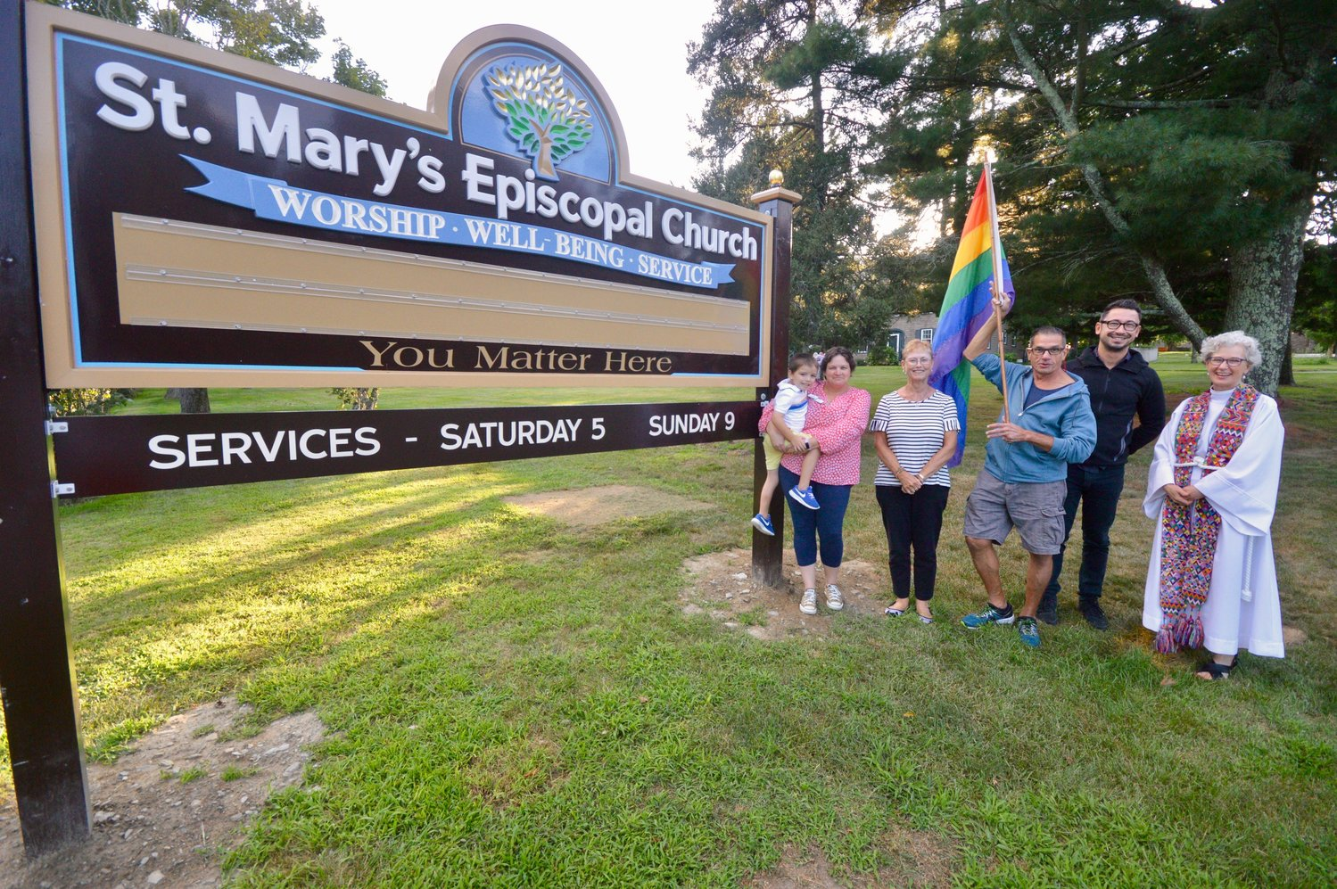 Along with some parishioners and church vestry members, Jennifer Pedrick (far right), rector of St. Mary's Episcopal Church, poses with the church's new sign and rainbow flag that welcomes everyone, including members of the LGBTQ community.