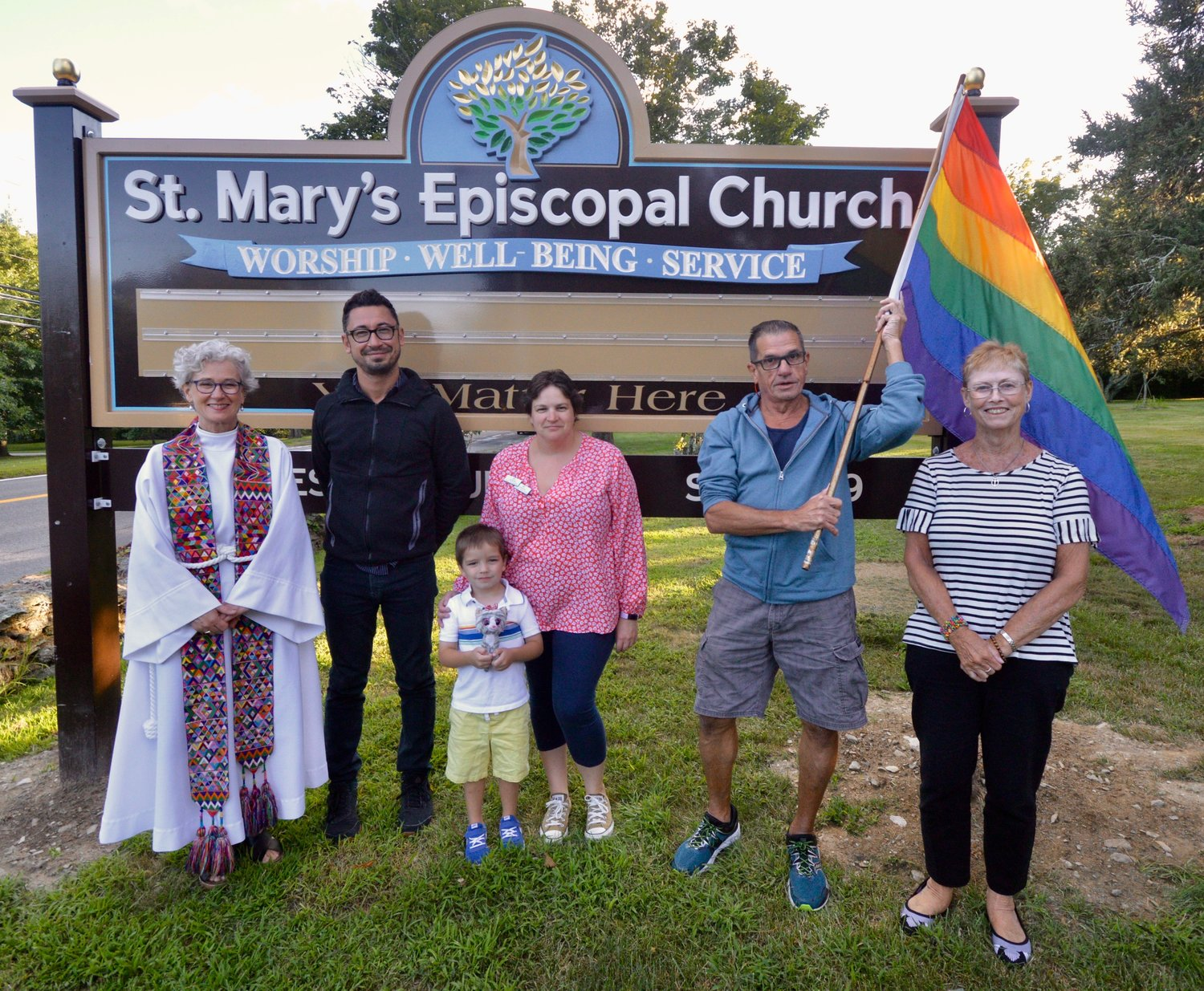 Along with some parishioners and church vestry members, Jennifer Pedrick (left), rector of St. Mary's Episcopal Church, poses with the church's new sign and rainbow flag that welcomes everyone, including members of the LGBTQ community.