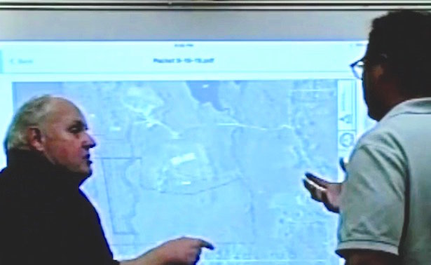 Moments after casting the lone vote that defeated the Fall River Rod and Gun Club's bid to put a solar project on its Sanford Road property, Planning Board member James Watterson, left, tells an engineer for the applicant where he thinks the project should have been located within the 150 acres.