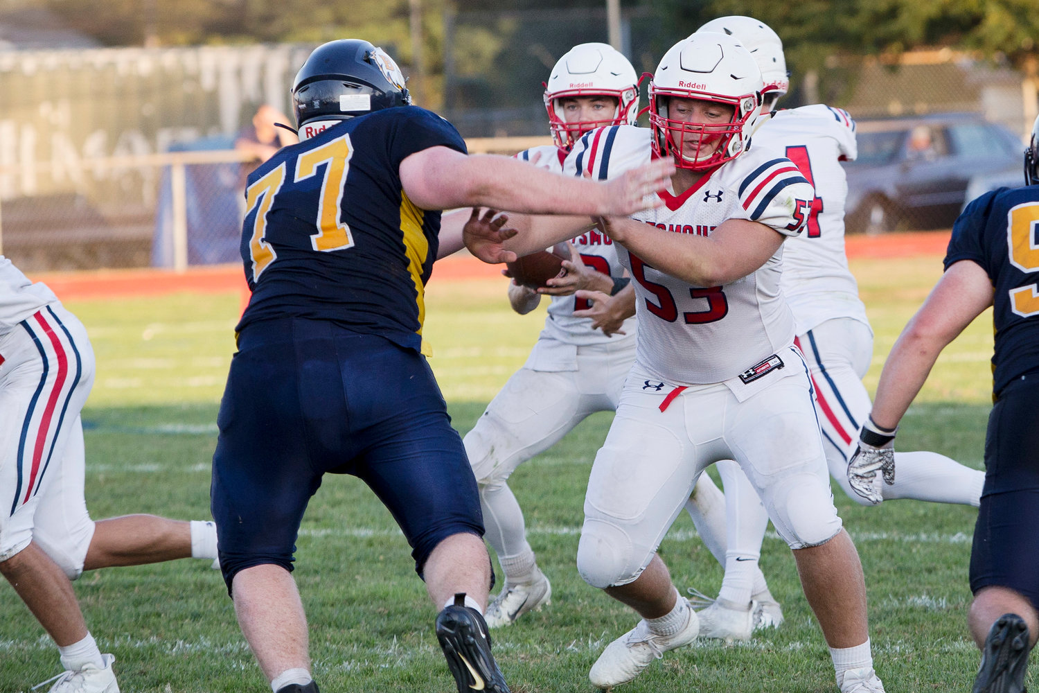 Harrison Russell (right) blocks a Barrington defender from reaching quarterback Benny Hurd.