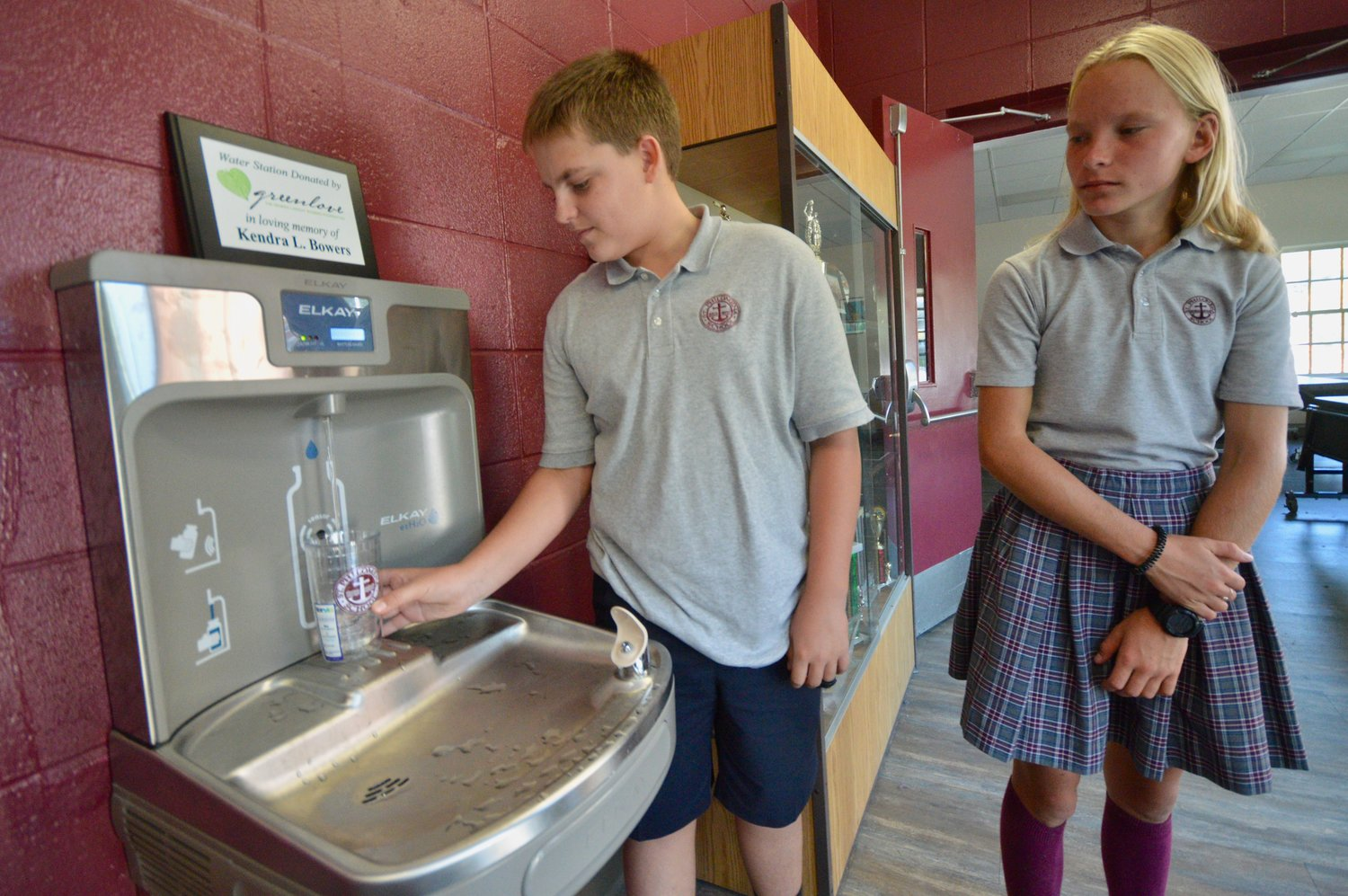 Chris DeSantis and Julia Pelczarski, both eighth-graders at St. Philomena School, try out the new water bottle filling station that was donated by the Greenlove Foundation.