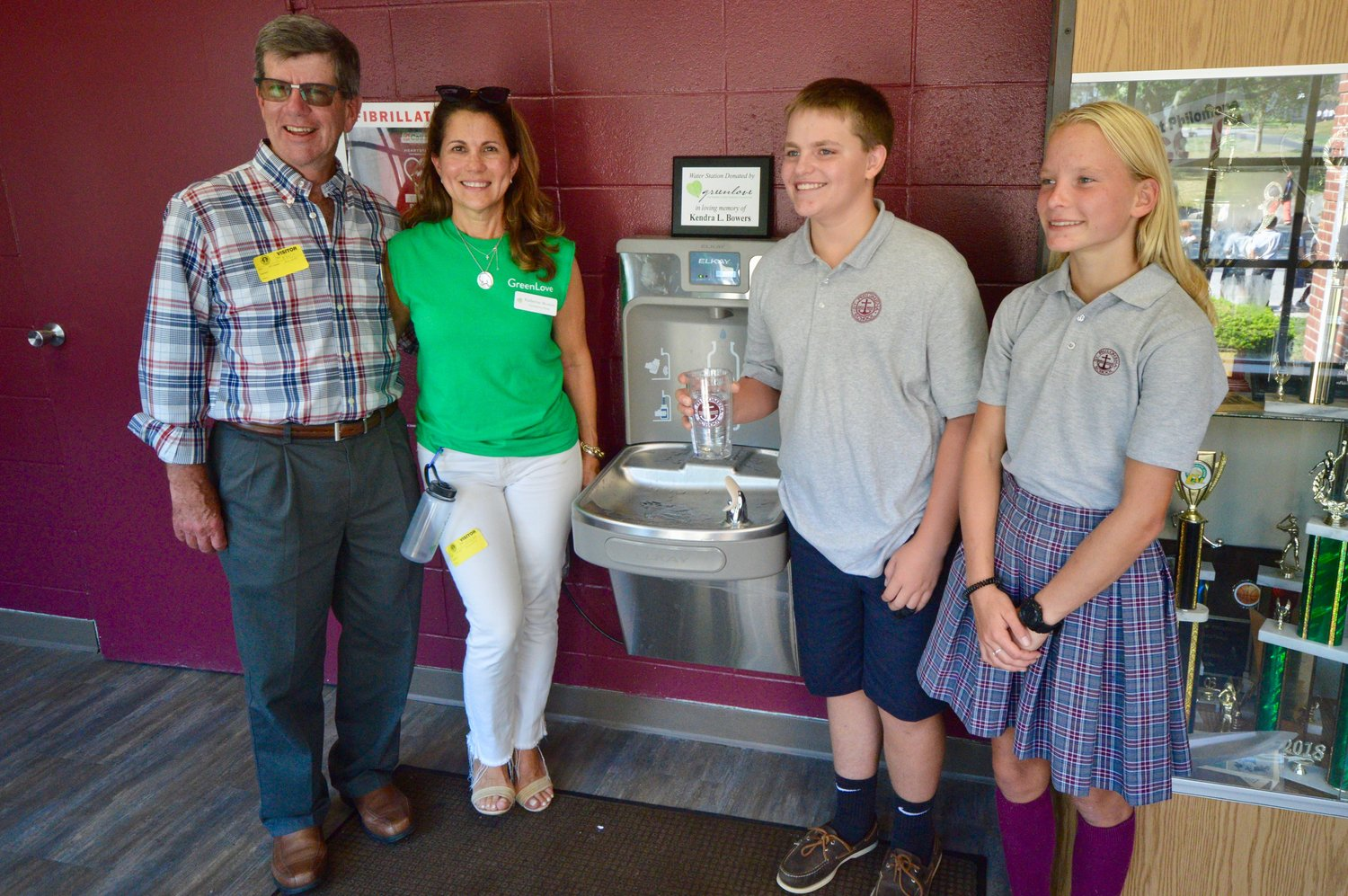 Michael and Katherine Bowers of the Greenlove Foundation pose with the new filling station along with St. Philomena School eighth-graders Chris DeSantis and Julia Pelszarski.
