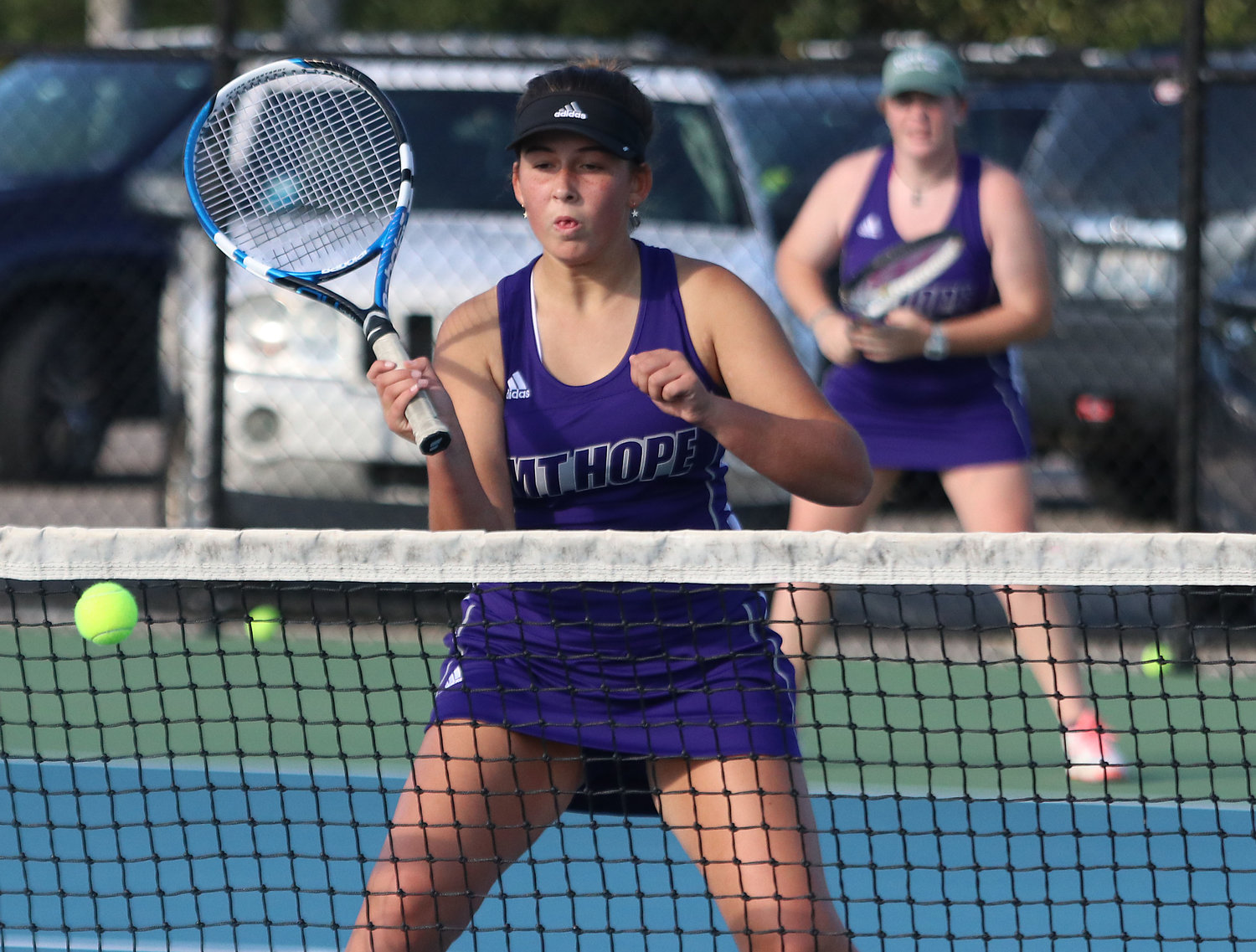 No. 1 doubles player Annie Kryzwicki drops a shot over the net for a winner with teammate Ellee Kopecky (back) looking on.