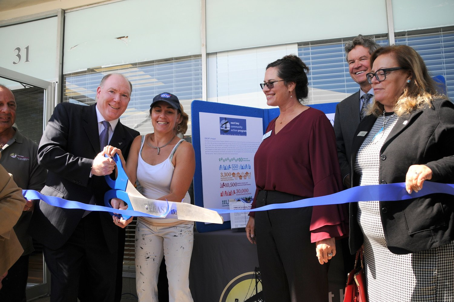 Thomas Joyce (second from left), East Bay Recovery Center director, helps with the cutting of the ribbon during ceremonies recently at the Railroad Avenue facility in Warren.